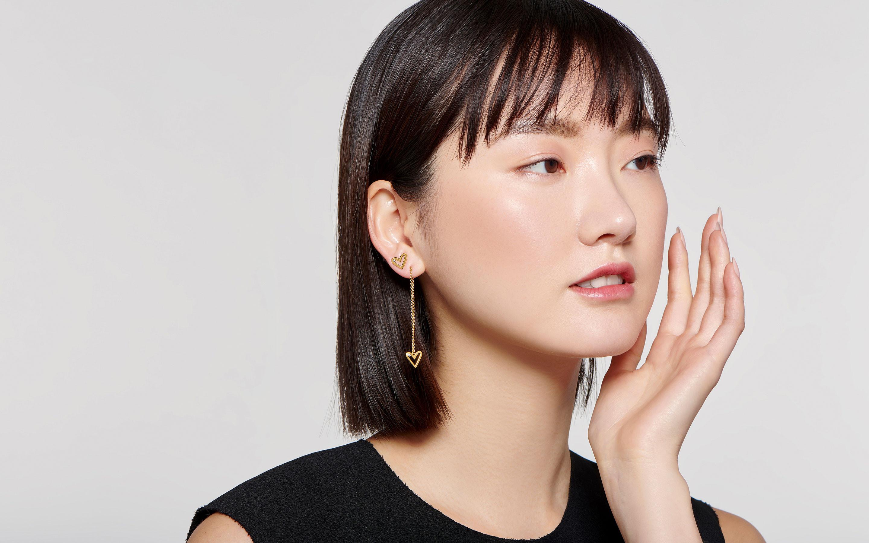 beautiful East Asian model wearing 22 karat gold stylish threader earrings with diamonds