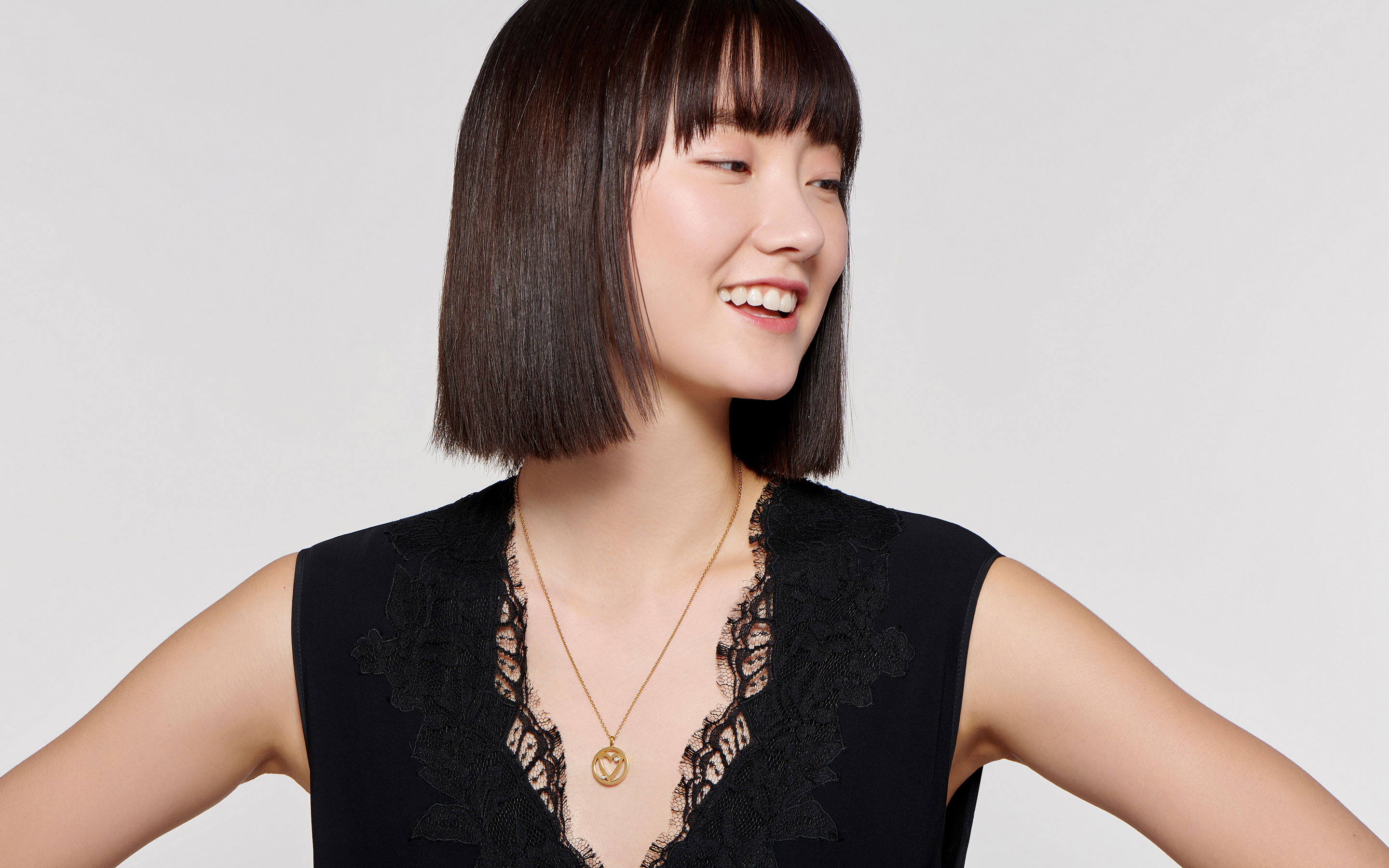 smiling East Asian model displaying stylish 22 karat gold necklace with open heart charm
