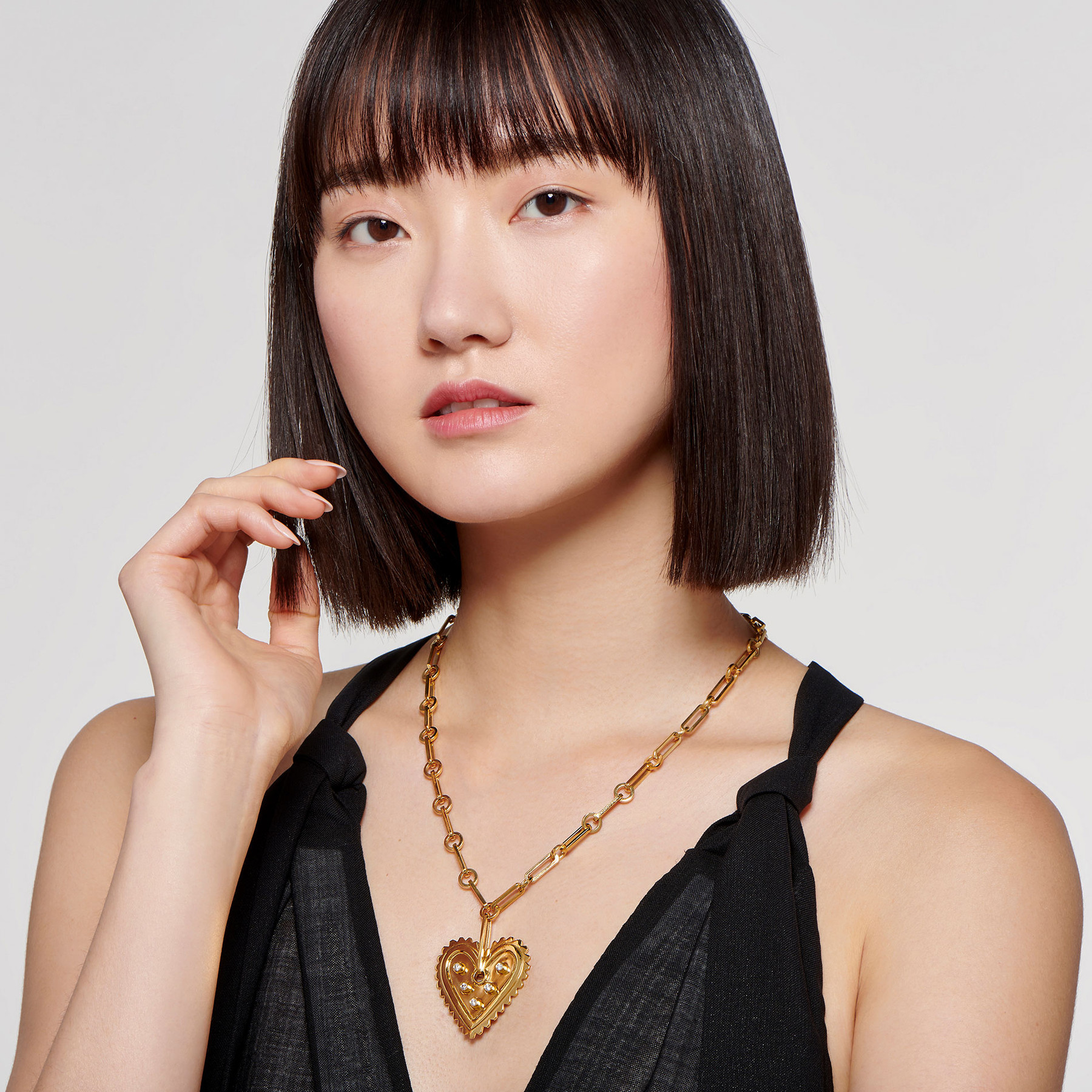 extravagant 22 karat gold necklace with diamond-studded heart pendant on stunning East Asian model