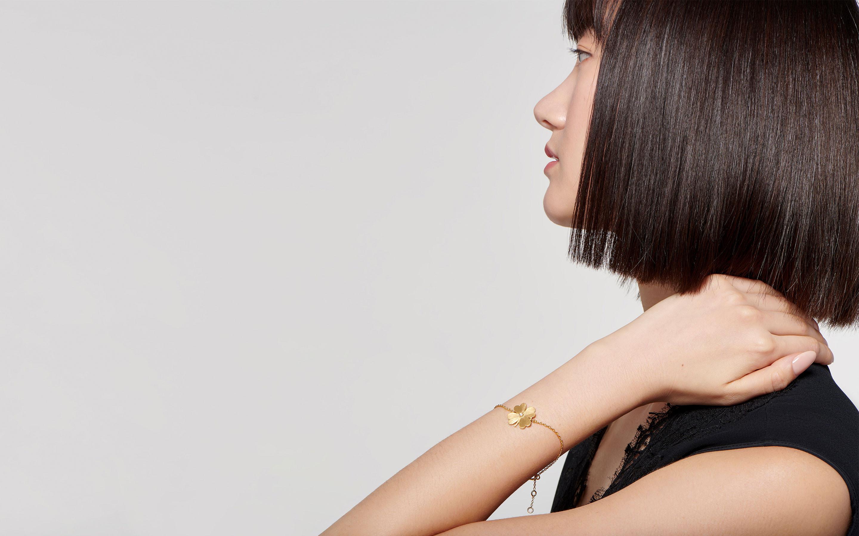 distant brunette displaying a delicate 22 karat satin gold bracelet in chic four leaf clover shape