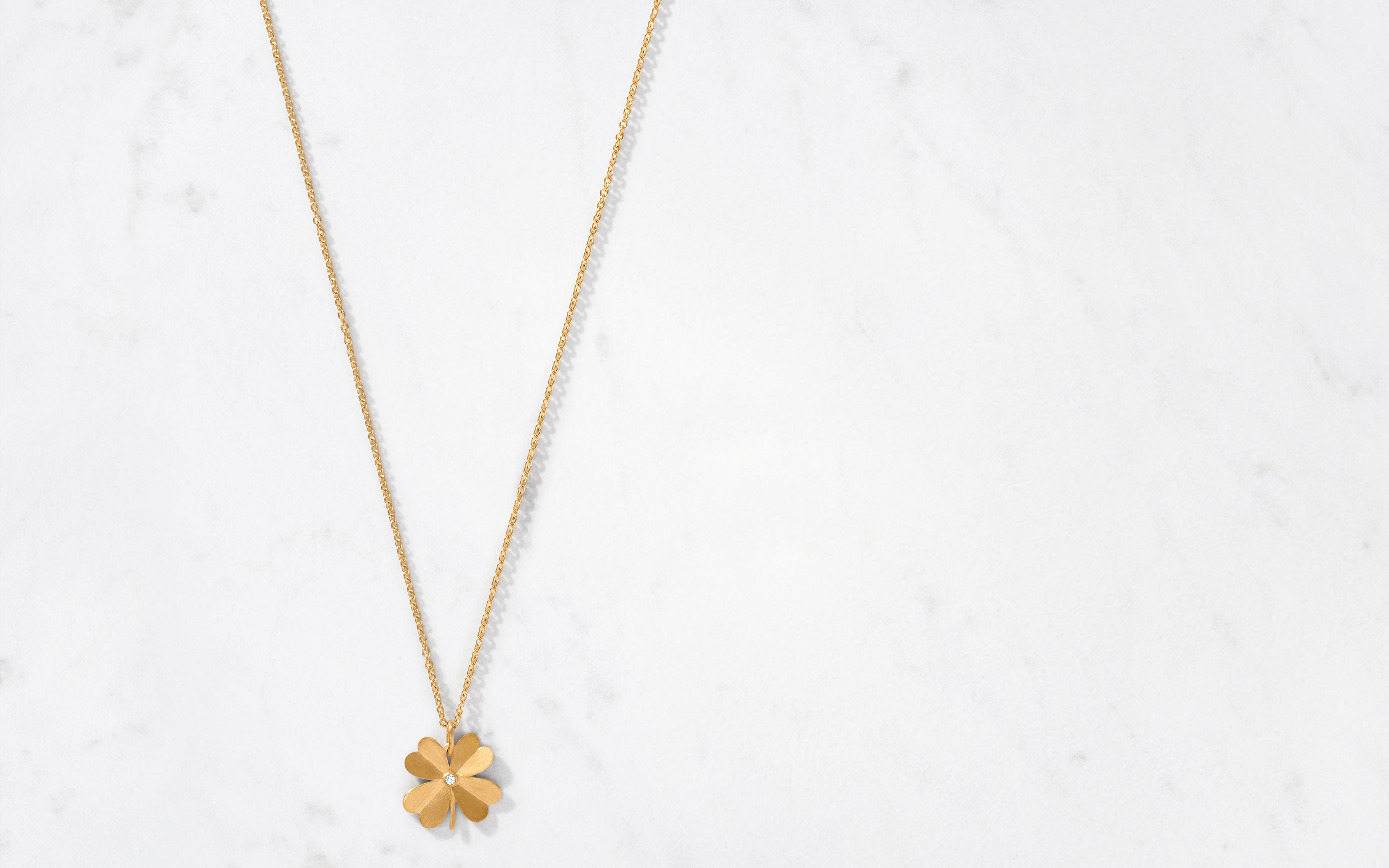 handcrafted 22 karat clover satin necklace with a marvelous center round cut diamond