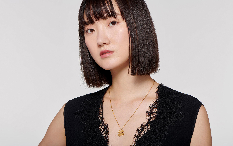 artisan 22 karat clover necklace with a beautiful center round cut diamond on a beautiful Asian Model