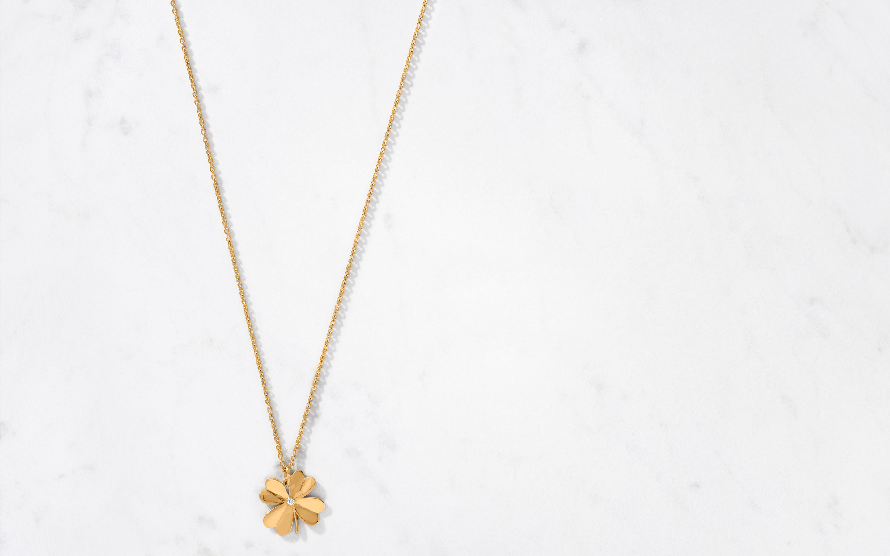 Expertly crafted 22 karat gold clover necklace with a beautiful center round cut diamond