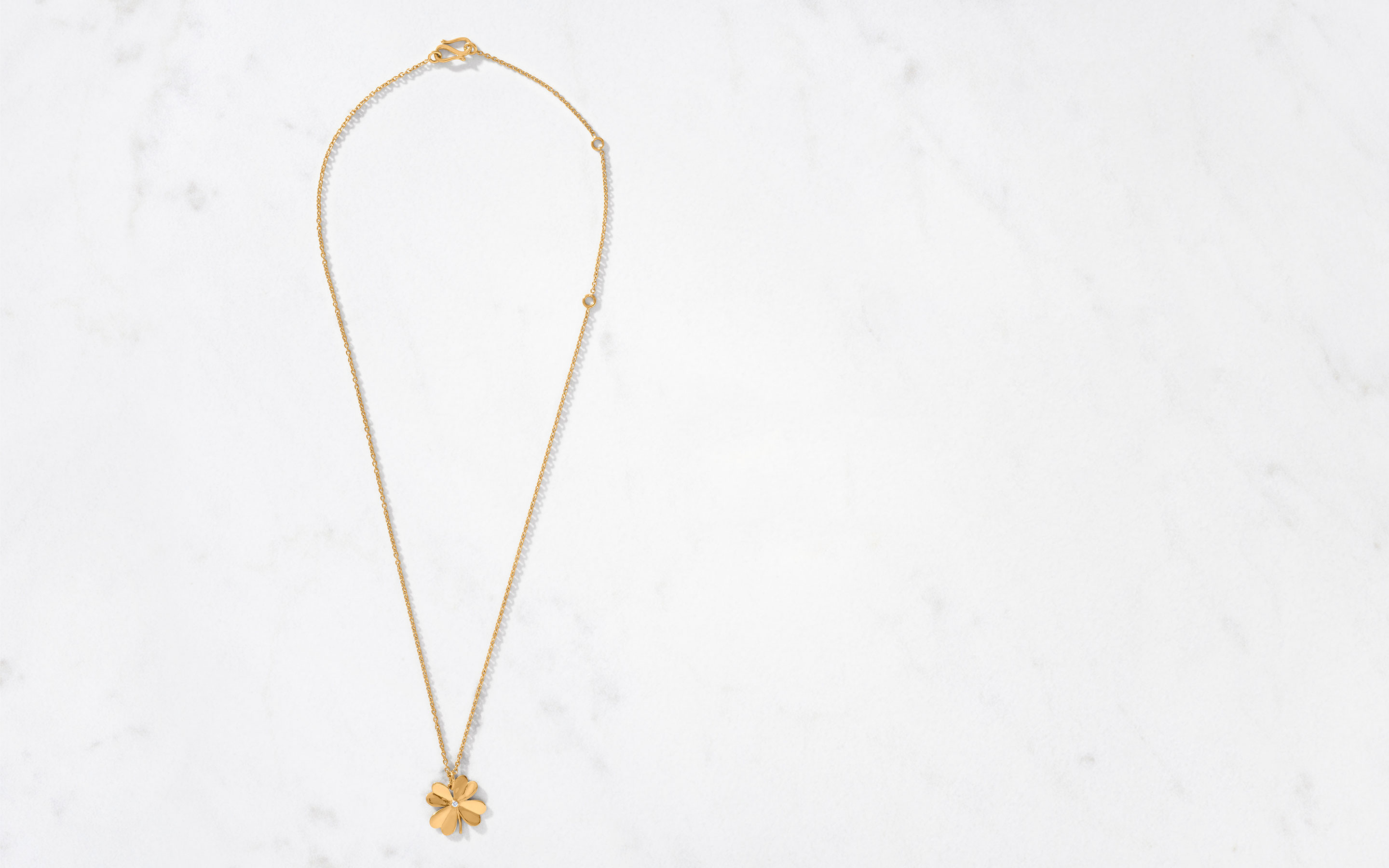 fancy 22 karat gold clover necklace polished finish  with a center cut round diamond