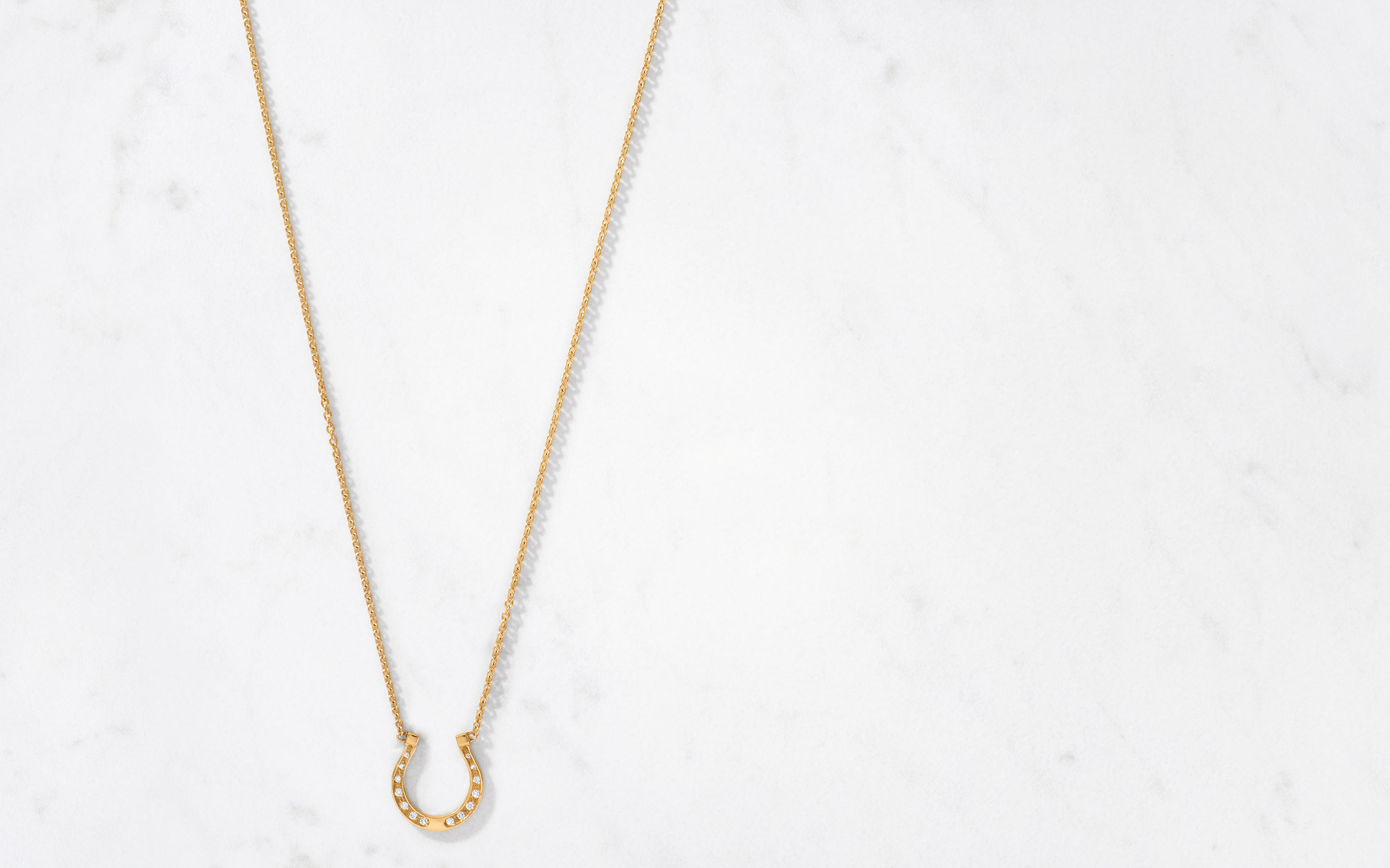 tasteful 22 karat gold necklace with a posh horseshoe pendant covered in 14 center cut round diamonds