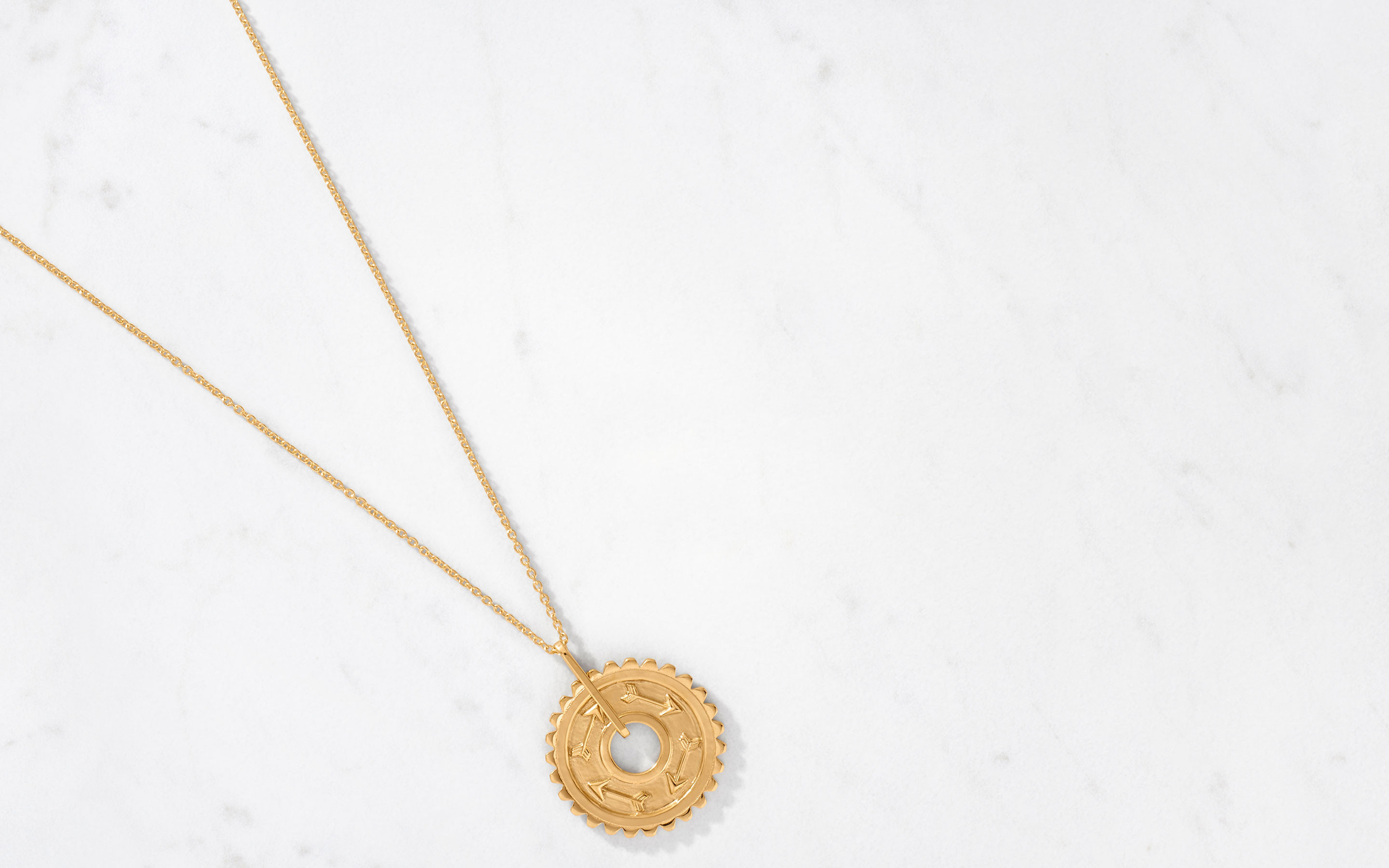 refined 22 karat gold talisman necklace with a spiral of arrows