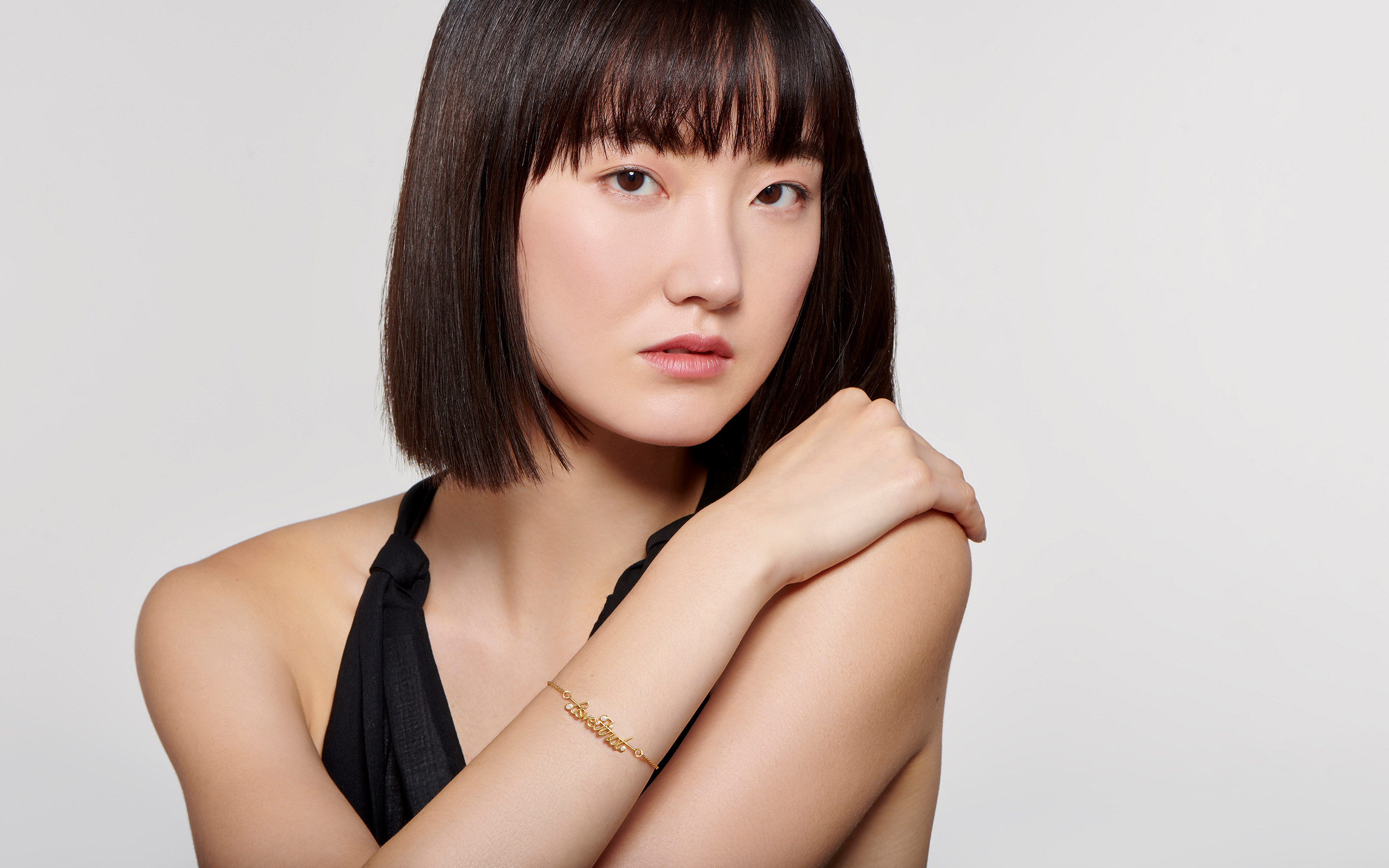 Intense Asian model flashing a magnificent 22 karat gold bracelet