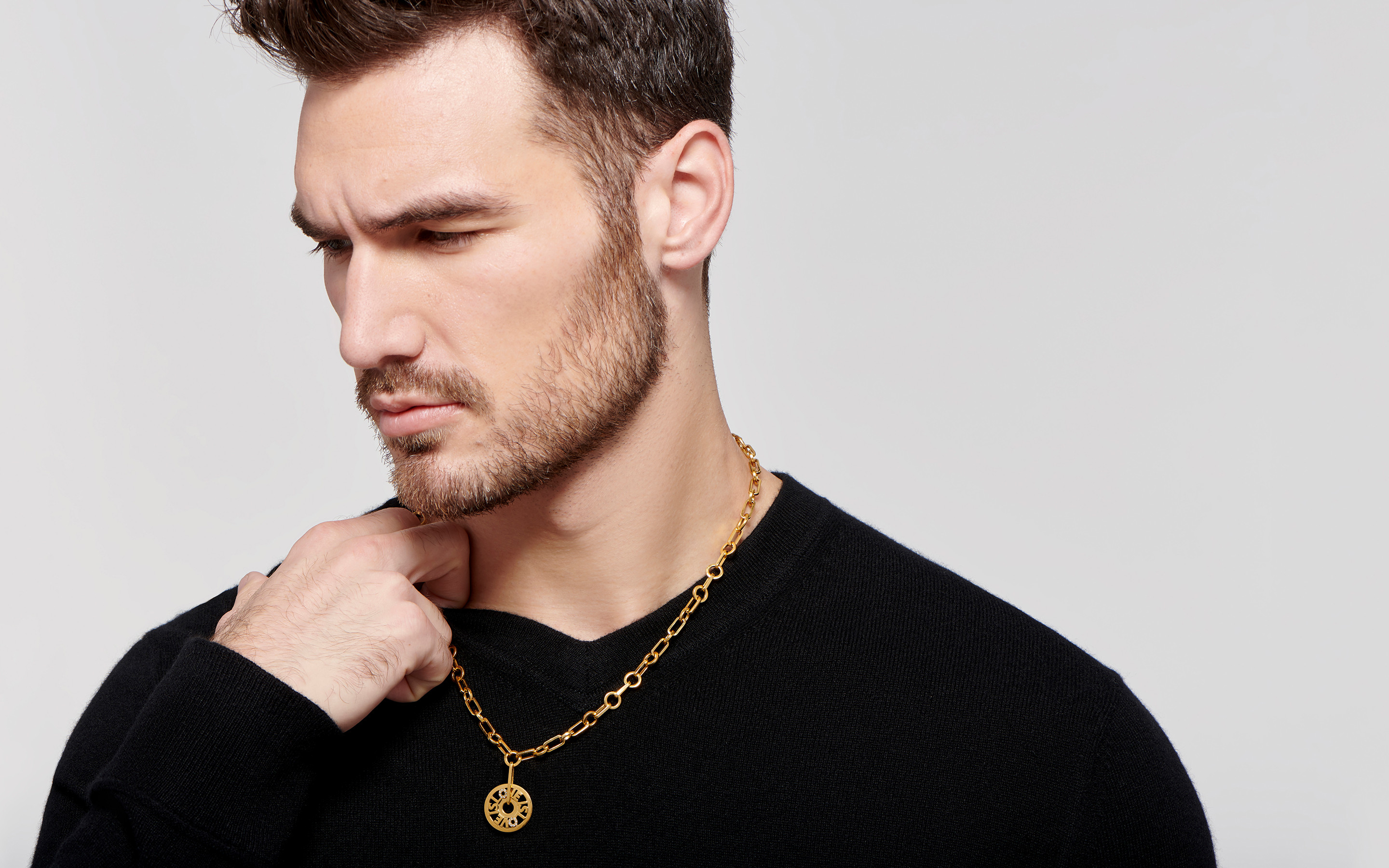 Steadfast  white male model wrapped in a gorgeous 22 carat gold necklace