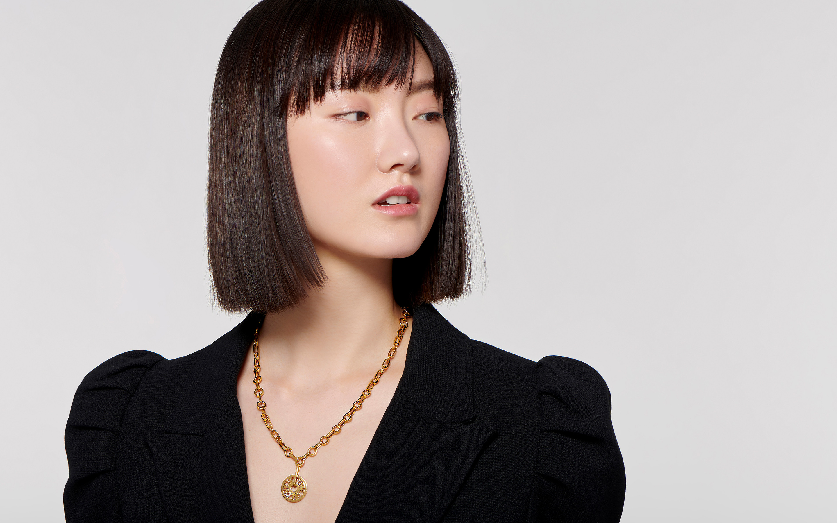 Stunning Asian model decorated with a love is love 22 karat gold necklace