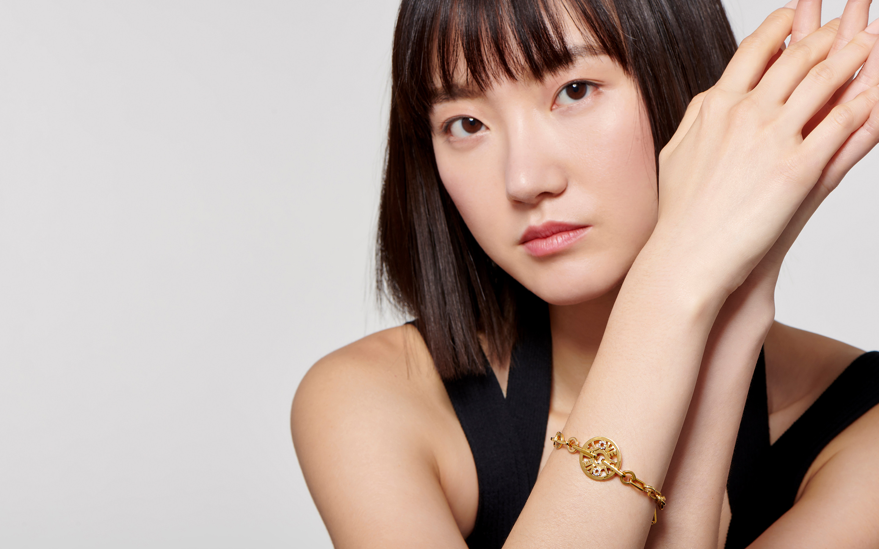 Glowing Asian model  brandishes a 22 carat gold bracelet