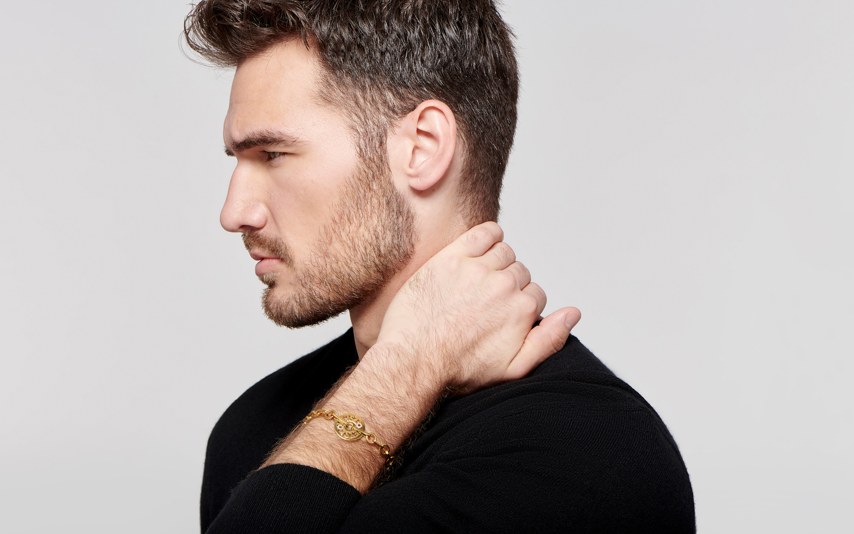 stunning white male model shows off a beautiful 22 karat  gold bracelet