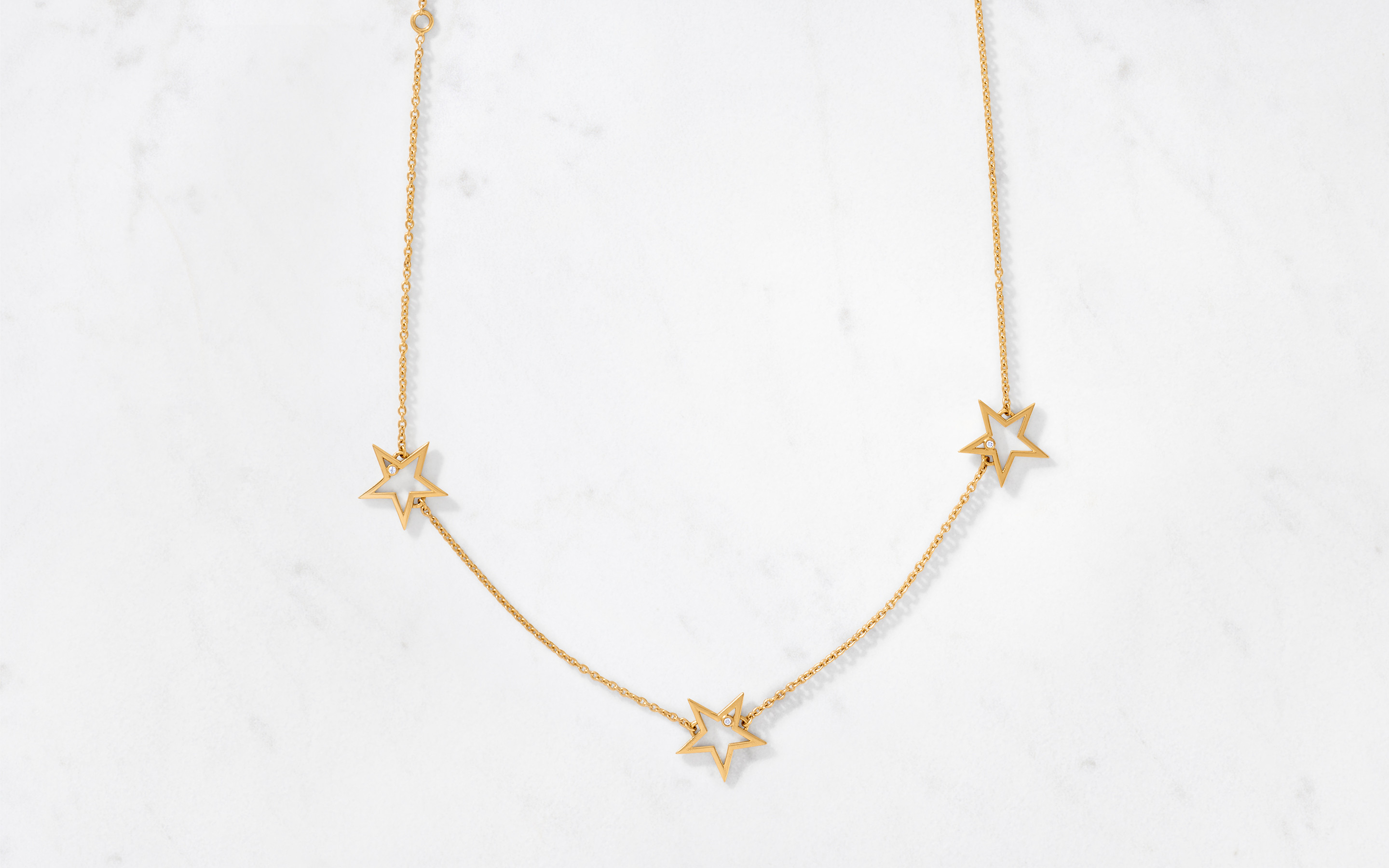 Delicate gold chain laying showing its stock of three  gold stars made of 22 karat gold