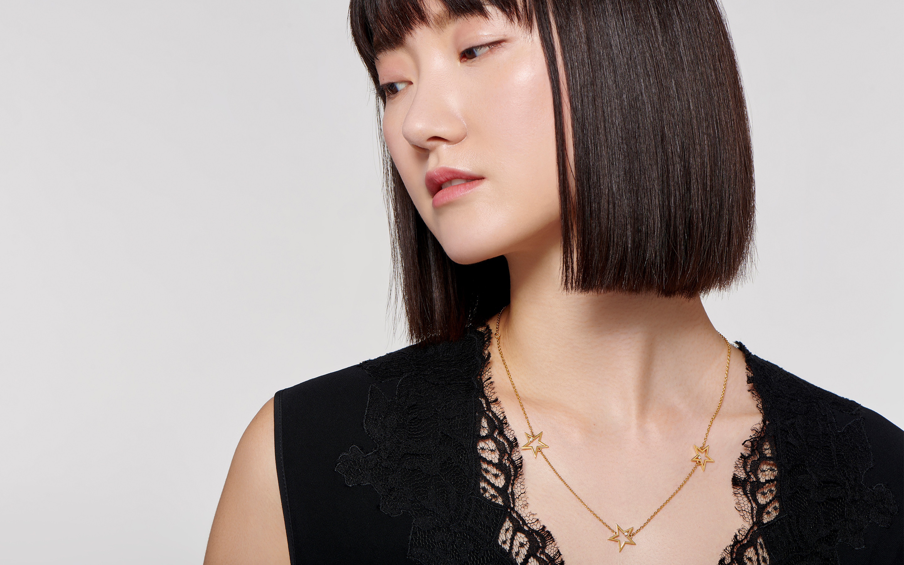 Asian woman with a bob cut sports a 22 karat gold chain decorated with golden stars