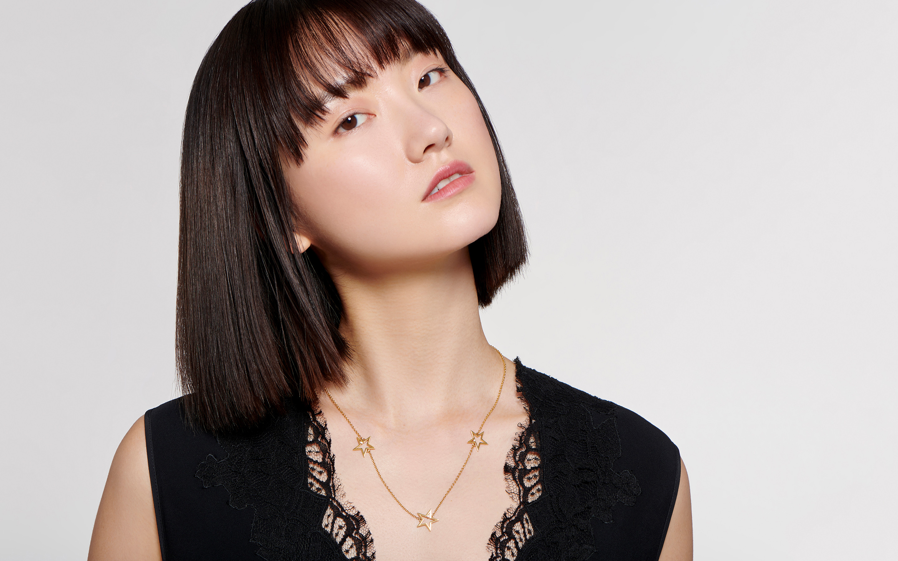Alluring Asian models dons a 22 karat gold necklace embolden by 3 golden stars