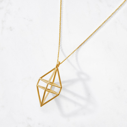 Our three-dimensional Cage Pendant feels like a modern version of an ancient talisman dangling from a delicate golden chain. Both beautifully handcrafted from 22 karat polished gold with a combined gold weight of around 20 grams.