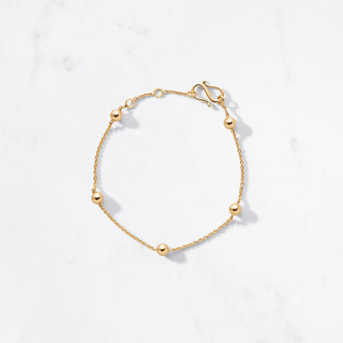 Delicate mini moons orbit your wrist with grace. Handcrafted from 22 karat polished gold with an adjustable chain and an approximate gold weight of 4.5 grams, Pavo Bracelet goes full circle.