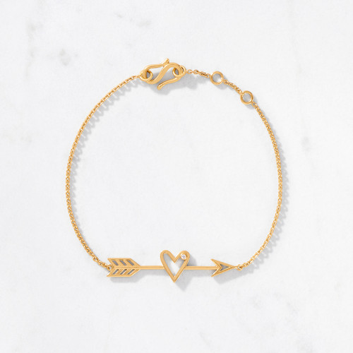 Aim for the heart with our Shooting Arrow Bracelet. Embrace iconic love symbols in gleaming 22 karat polished gold with a sparkling round-cut diamond tucked neatly into the curve of the heart. Handcrafted of approximately 4 grams of gold.