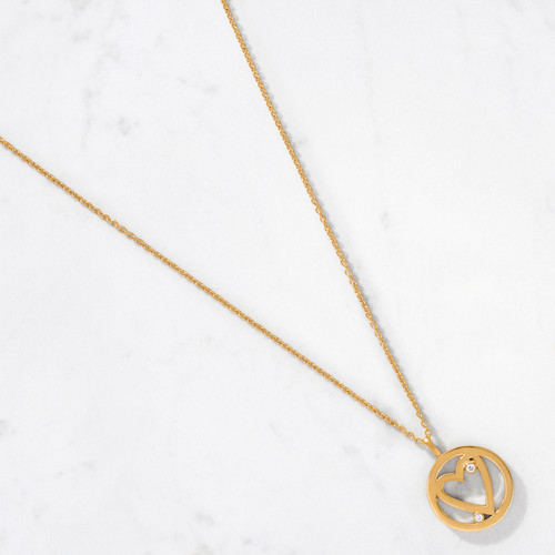 Our Open Heart Pendant is inspired by the expansiveness of true love. Handcrafted from 22 karat polished gold with an approximate gold weight of 10.5 grams, this pendant contains two round cut diamonds all set inside a symbolic eternal circle.