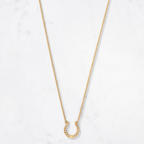 Our Golden Horseshoe Diamond Necklace, with a gold weight of approximately 6.5 grams, is a timeless symbol of good luck and protection. Crafted by hand from 22 karat gold and set with 14 round cut diamonds of graduating sizes.