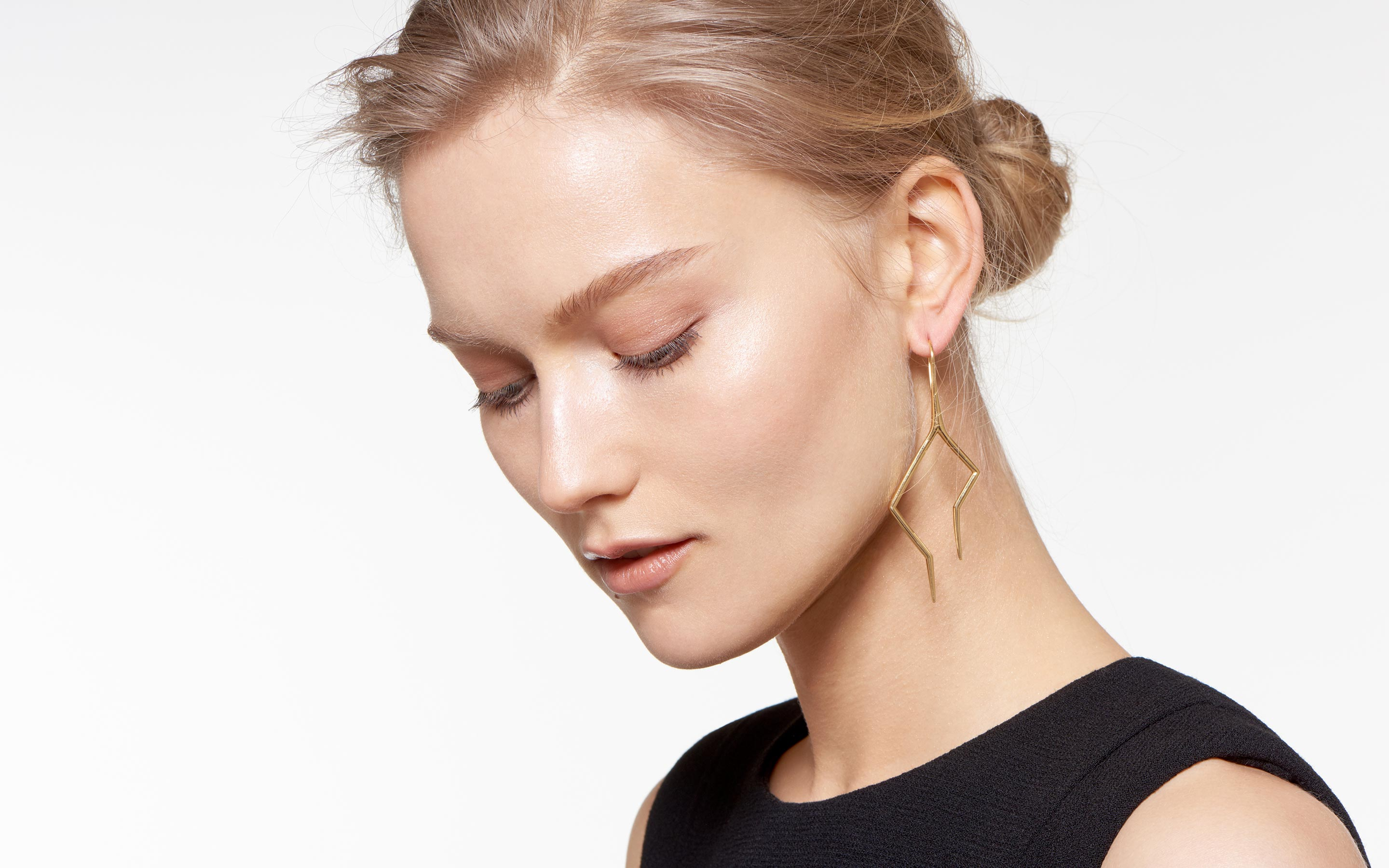 elegant model with 22 karat gold hook earrings fashioned into contemporary lightning bolts