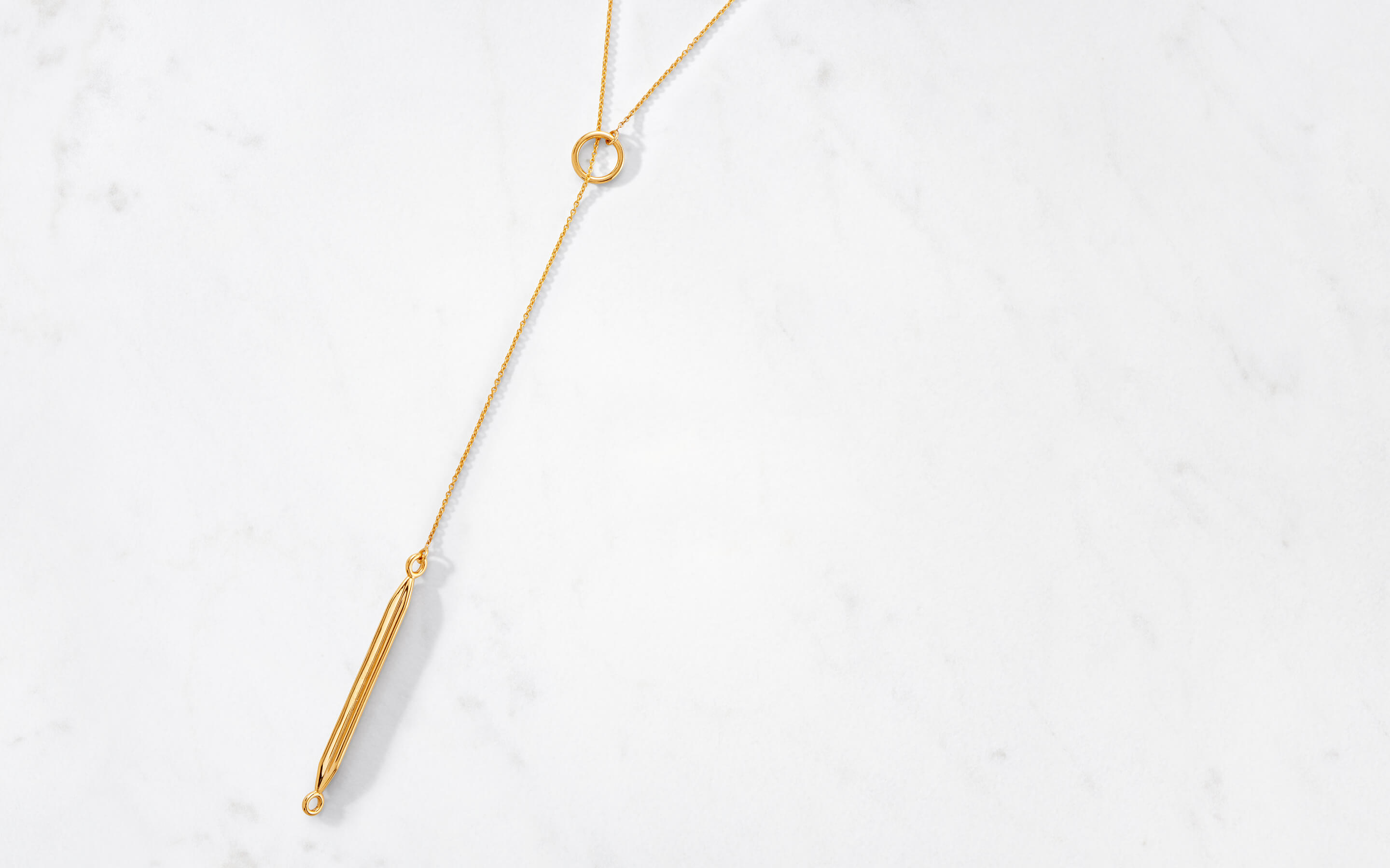 modern 22 karat gold necklace in lariat-style with obelisk charm