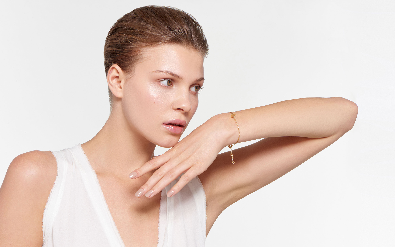 model posing dramatically wearing 22 karat gold bracelet containing cage charm