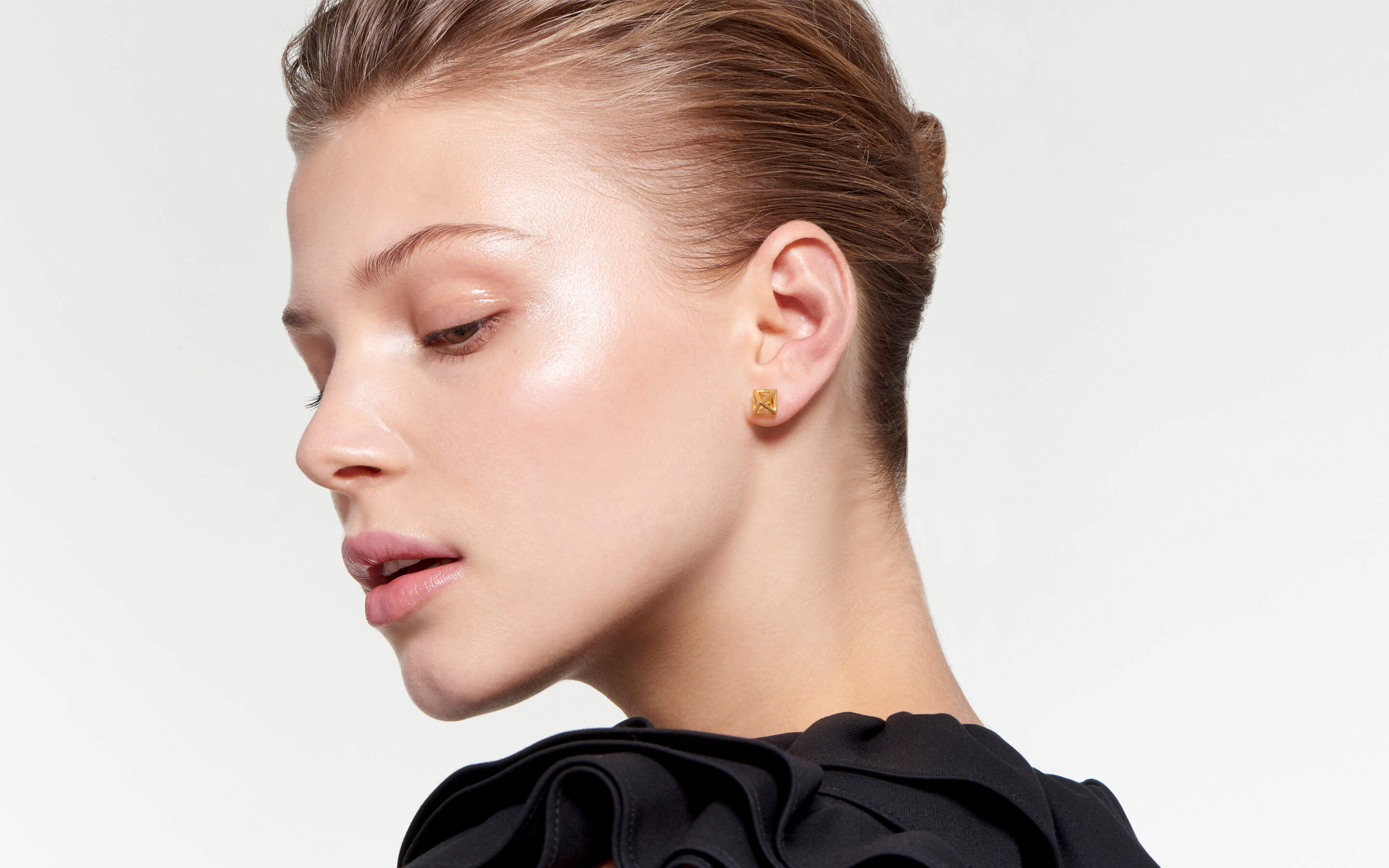 enigmatic model wearing glowing geometric stud earrings made of 22 karat polished gold