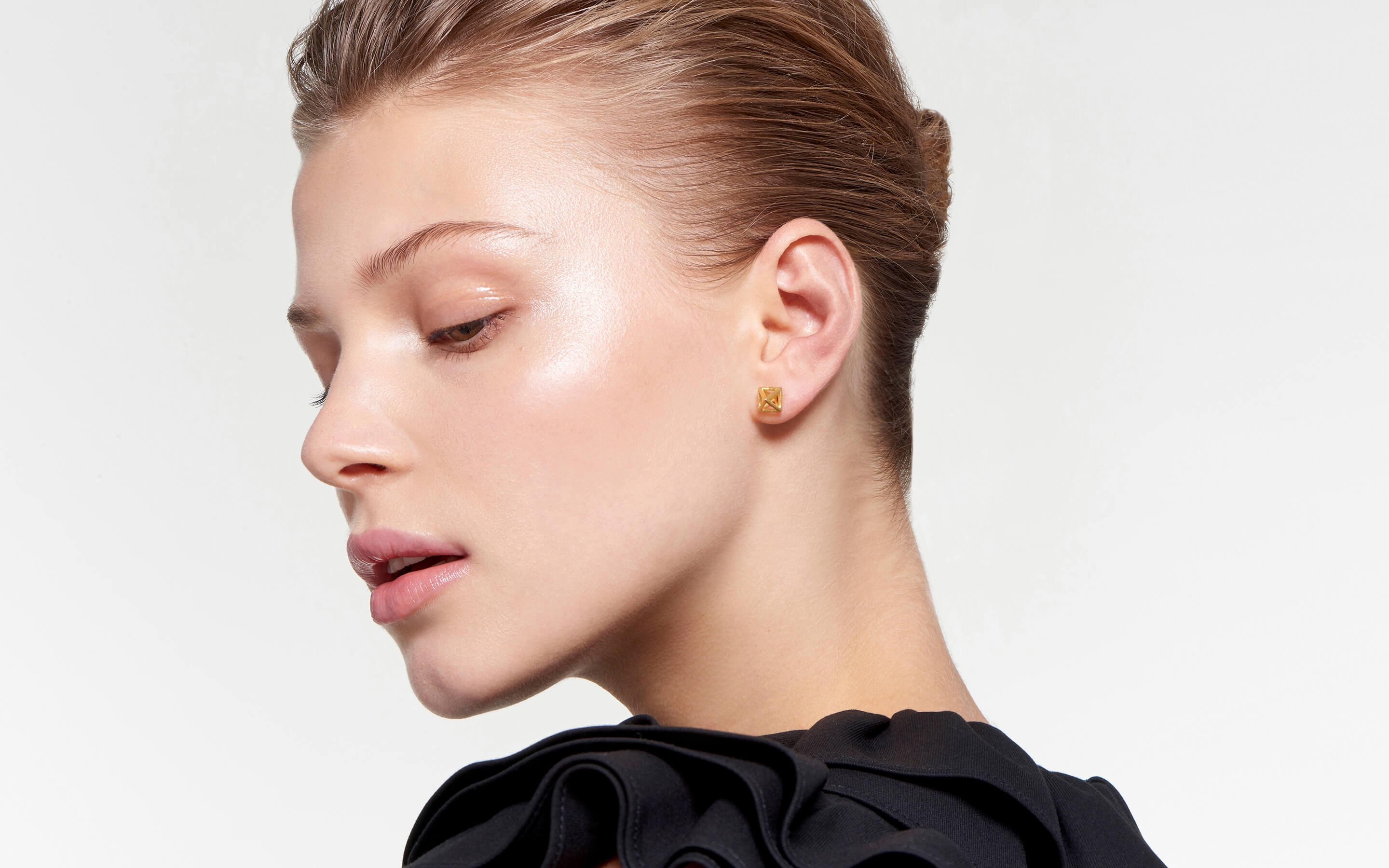 22 karat gold stud earrings with geometric cages in satin finish on stunning model
