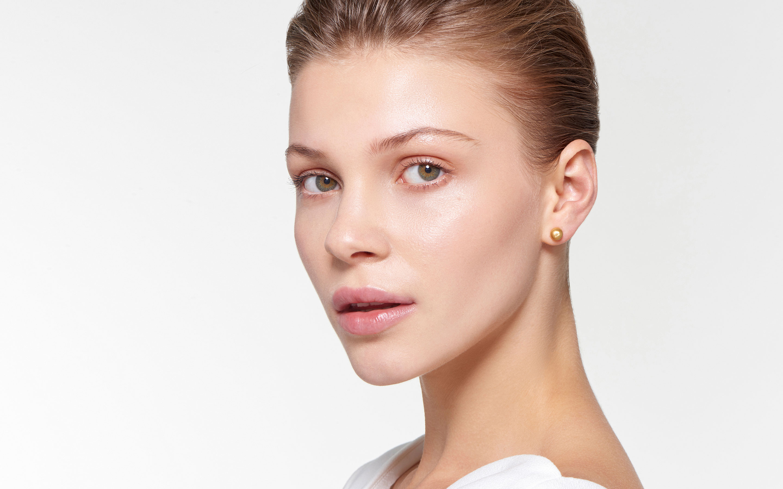 attractive model wearing shining spherical stud earrings of 22 karat gold satin finish