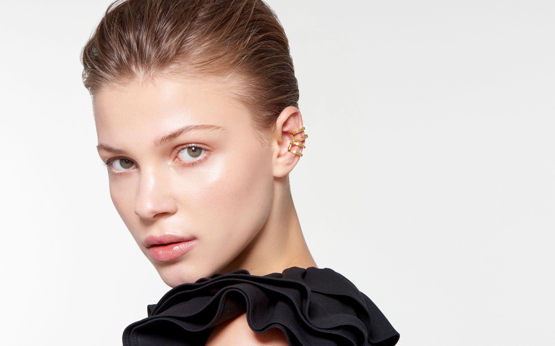 graceful female model wearing stylish ear cuff made of 22 karat gold in polished finish