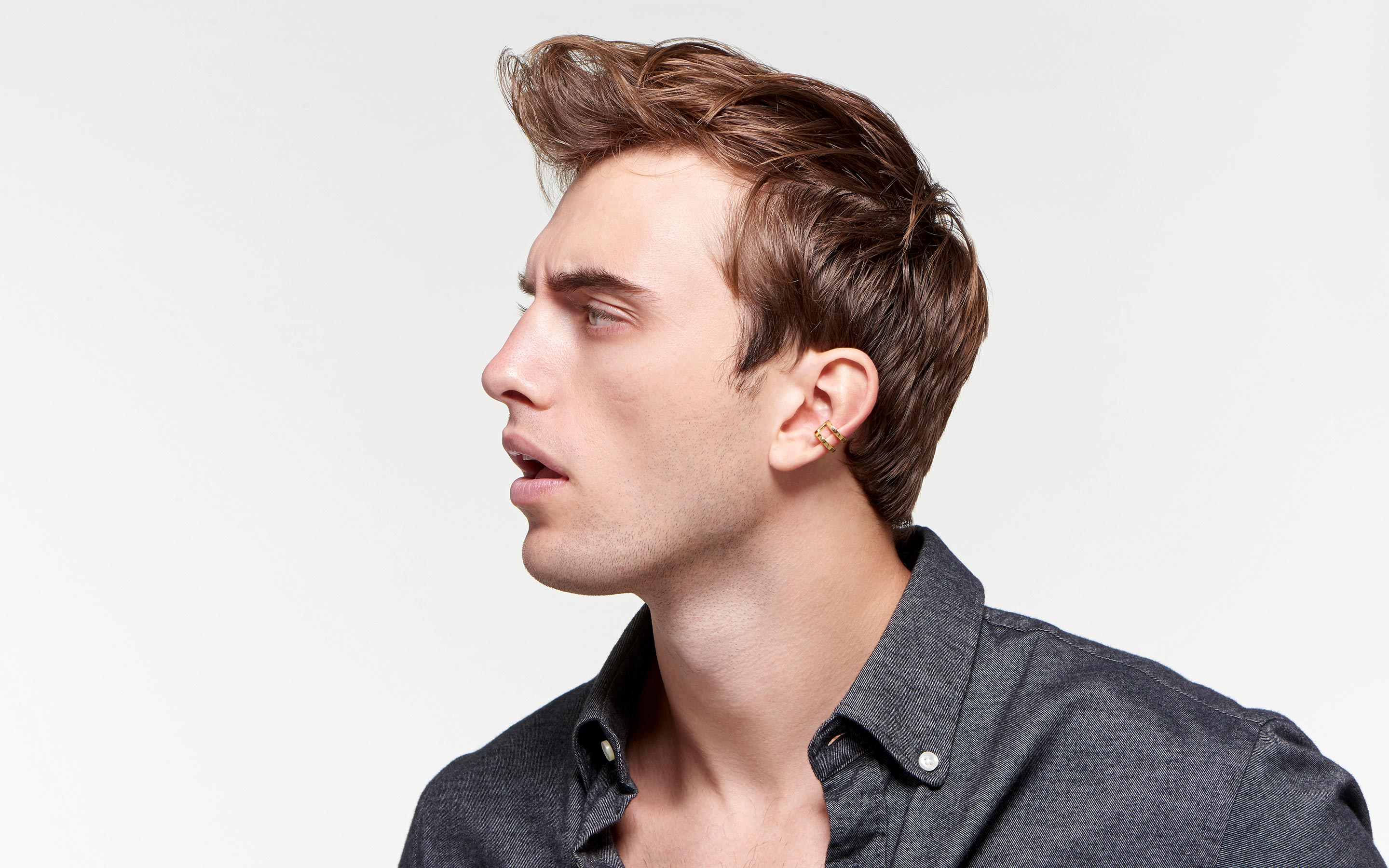 winsome male model displaying lustrous contemporary ear cuff made of 22 karat polished gold