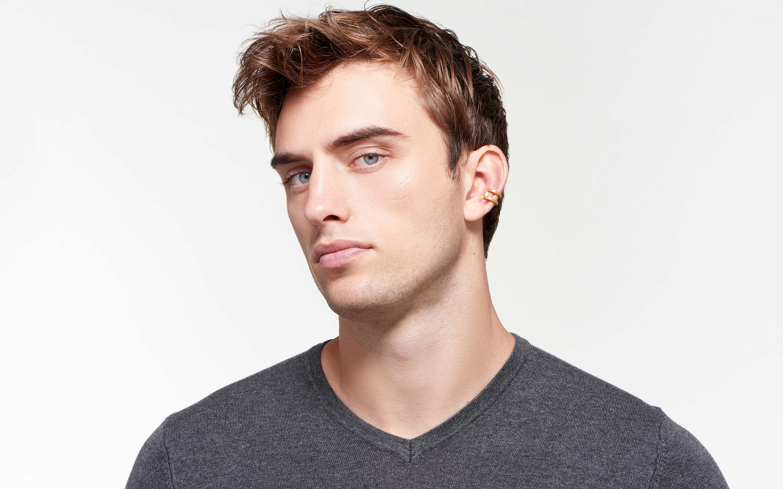 lustrous 22 karat satin gold ear cuff on handsome male model