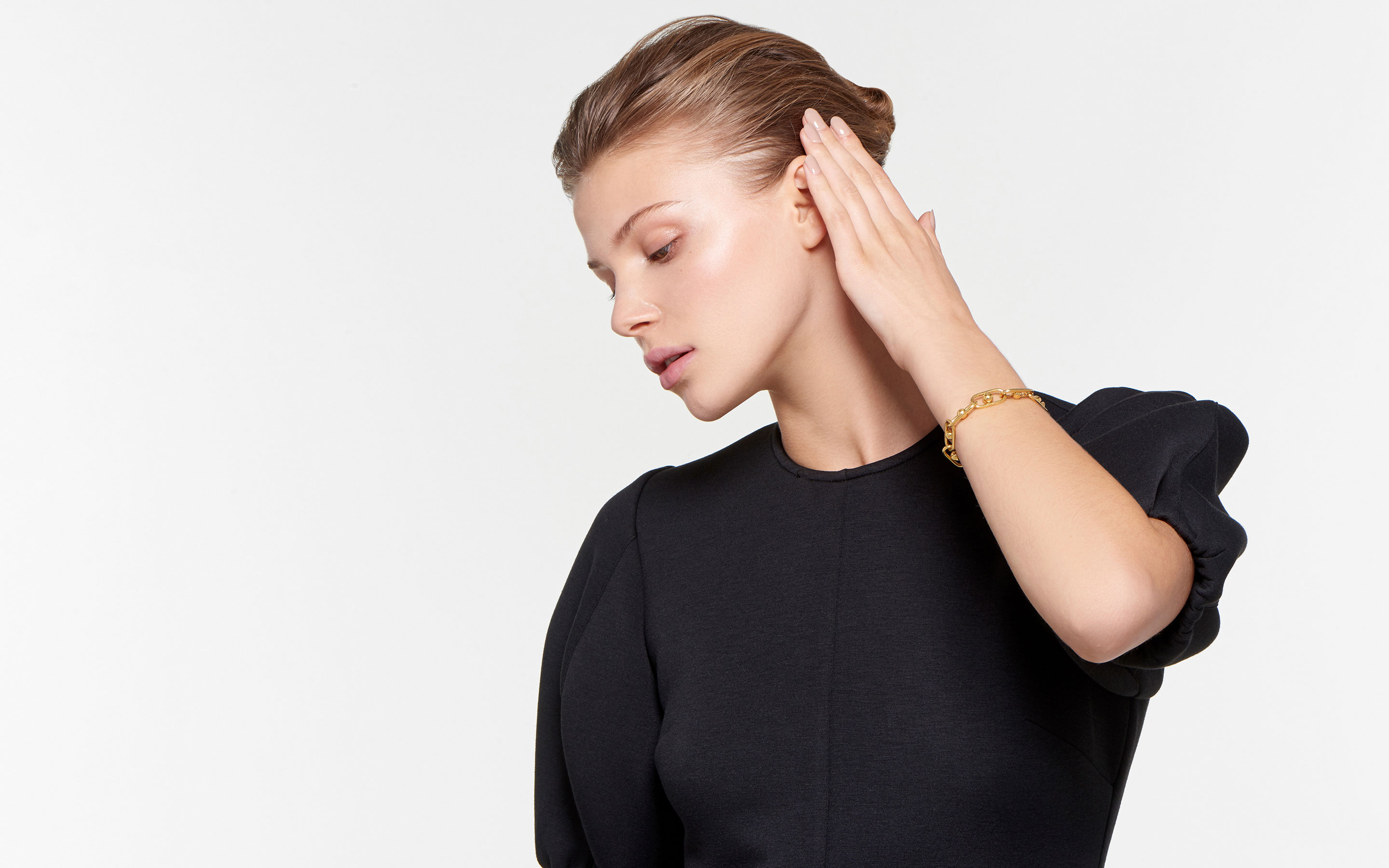 stunning model in profile sporting 22 karat gold bracelet with lunar-style globes suspended in ovular links