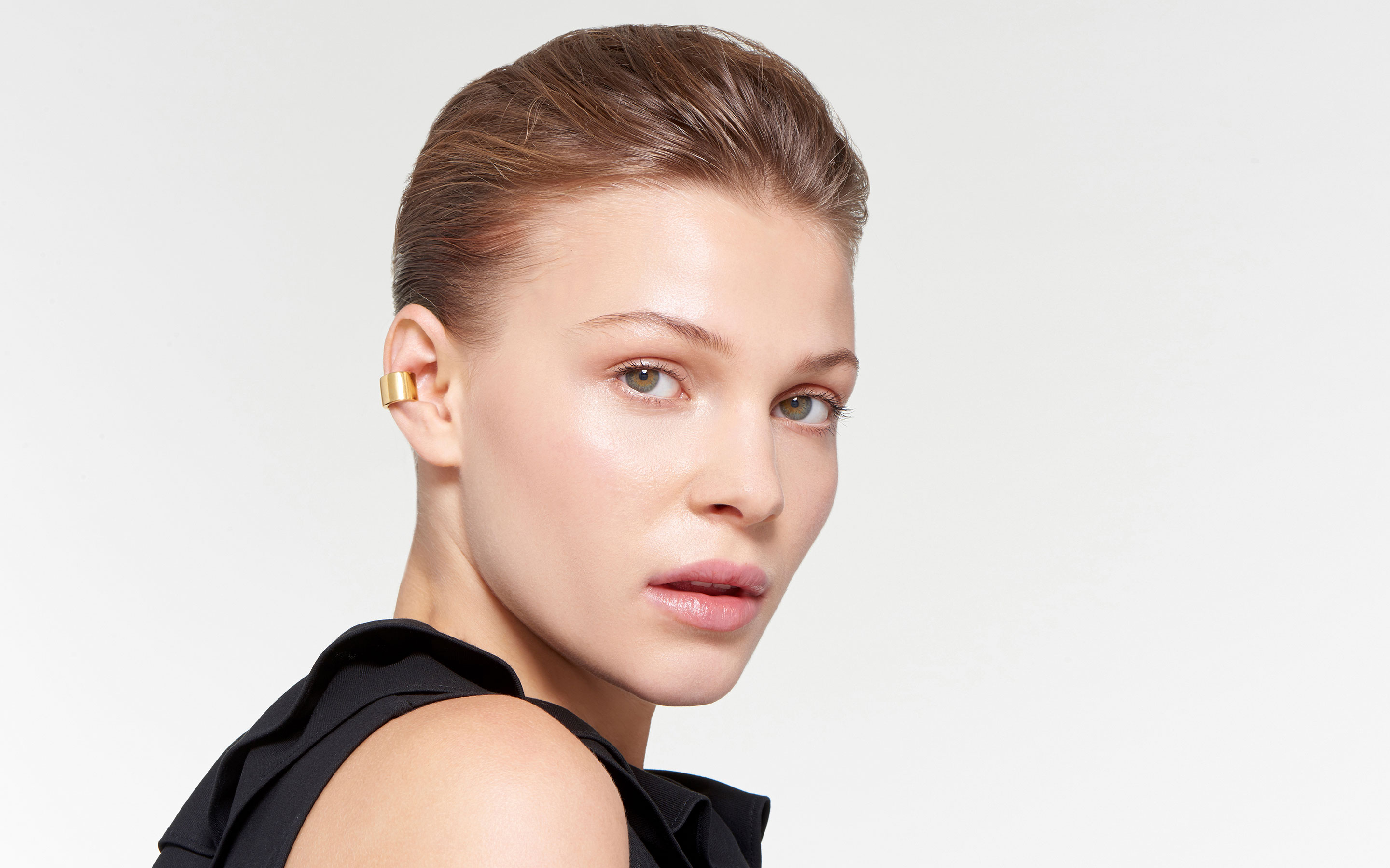 stylish model highlighting golden ear cuff fashioned of 22 karat gold