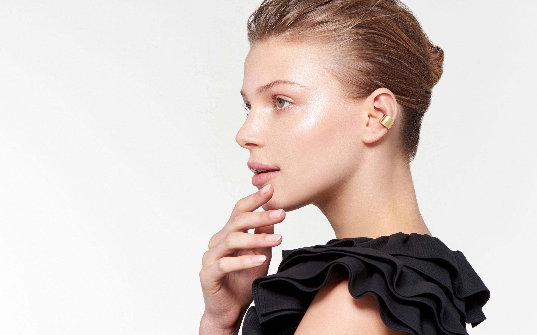 lissome female model wearing trendy polished ear cuff made of 22 karat gold