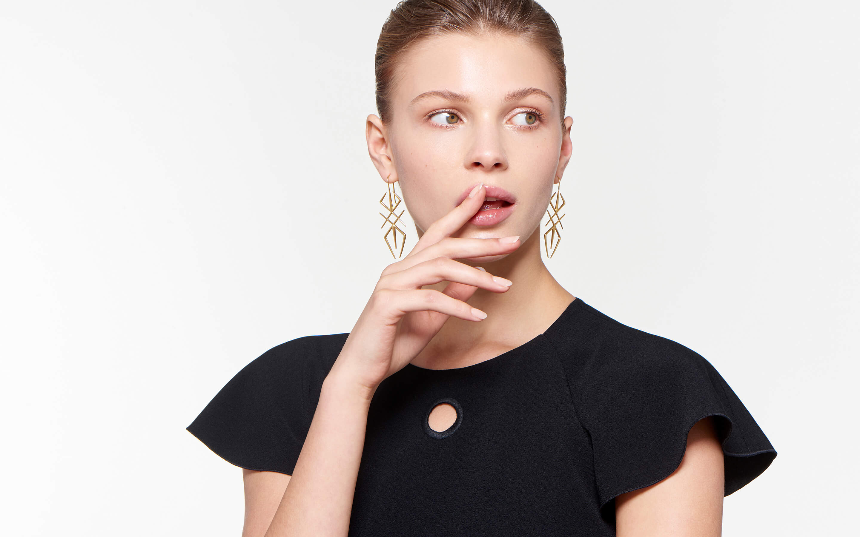 lovely model staring enigmatically wearing gleaming 22 karat gold earrings formed into artistic spiders