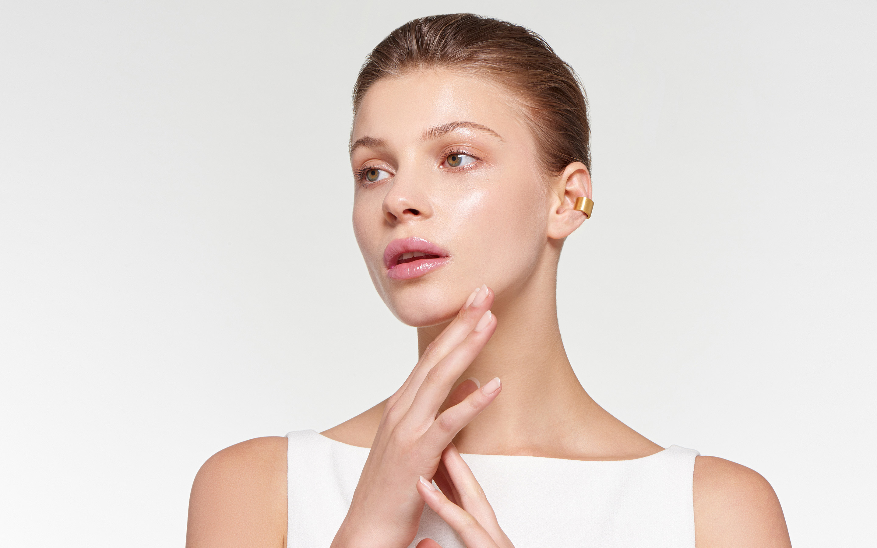 flaming ear cuffs made of 22 karat gold on elegant model gazing into the distance