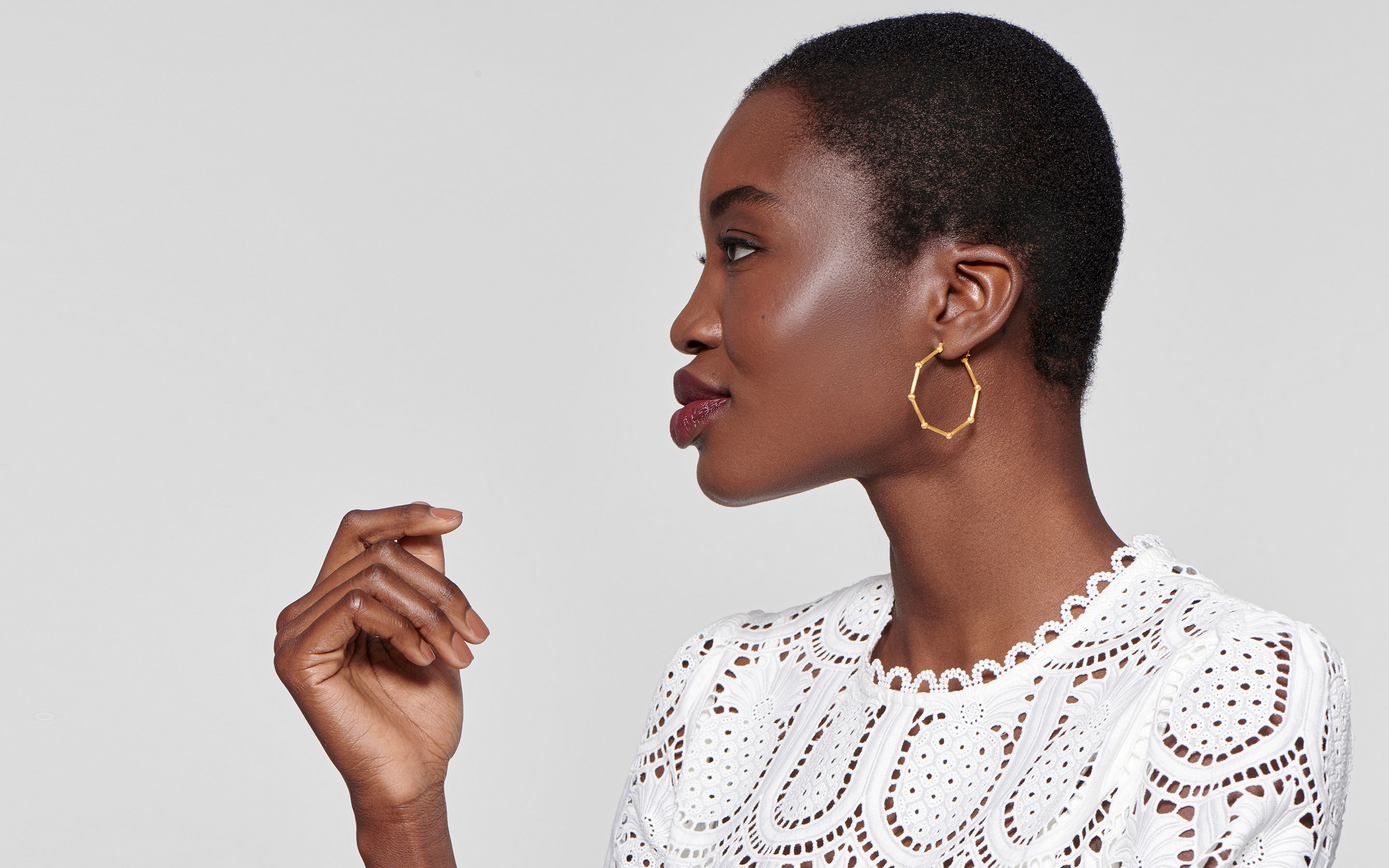 statuesque black model presenting luminous hoop style earrings made of 22 karat gold in satin finish
