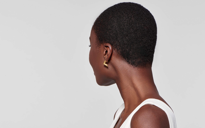 reverse view of black model showcasing geometric earrings in 22 karat polished gold