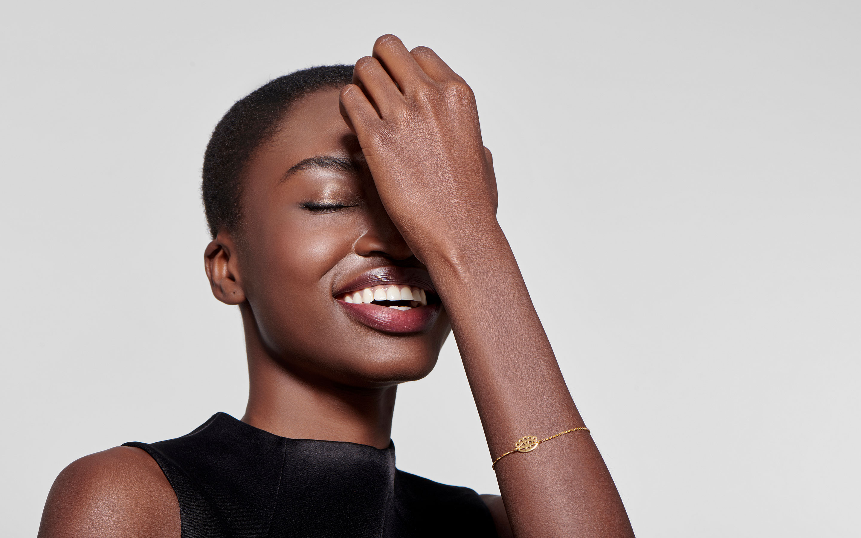 laughing black woman modeling 22 karat gold bracelet with floral evil eye charm in small size