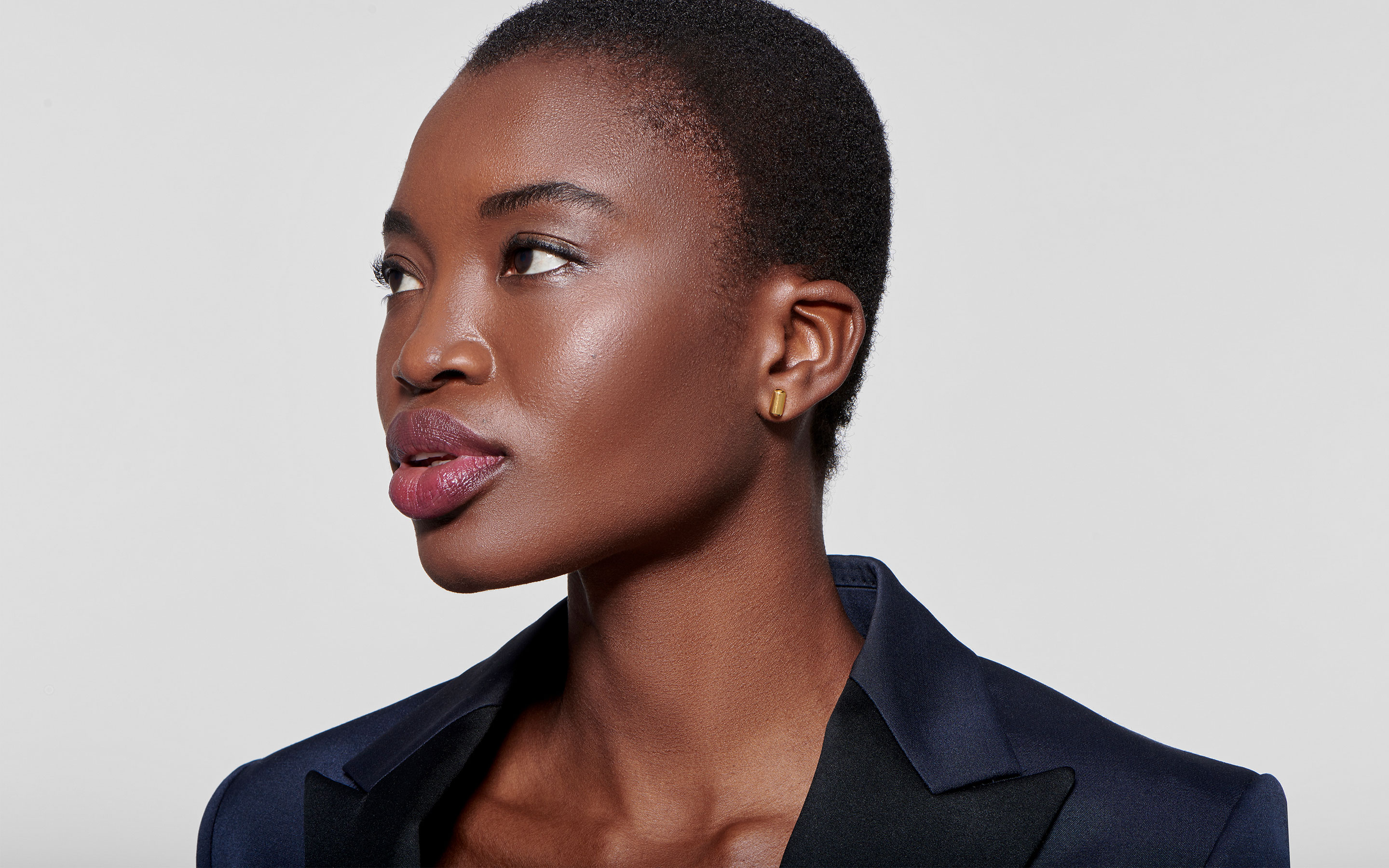 graceful black model looking pensively to the side with linear 22 karat polished gold earrings molded into barrels