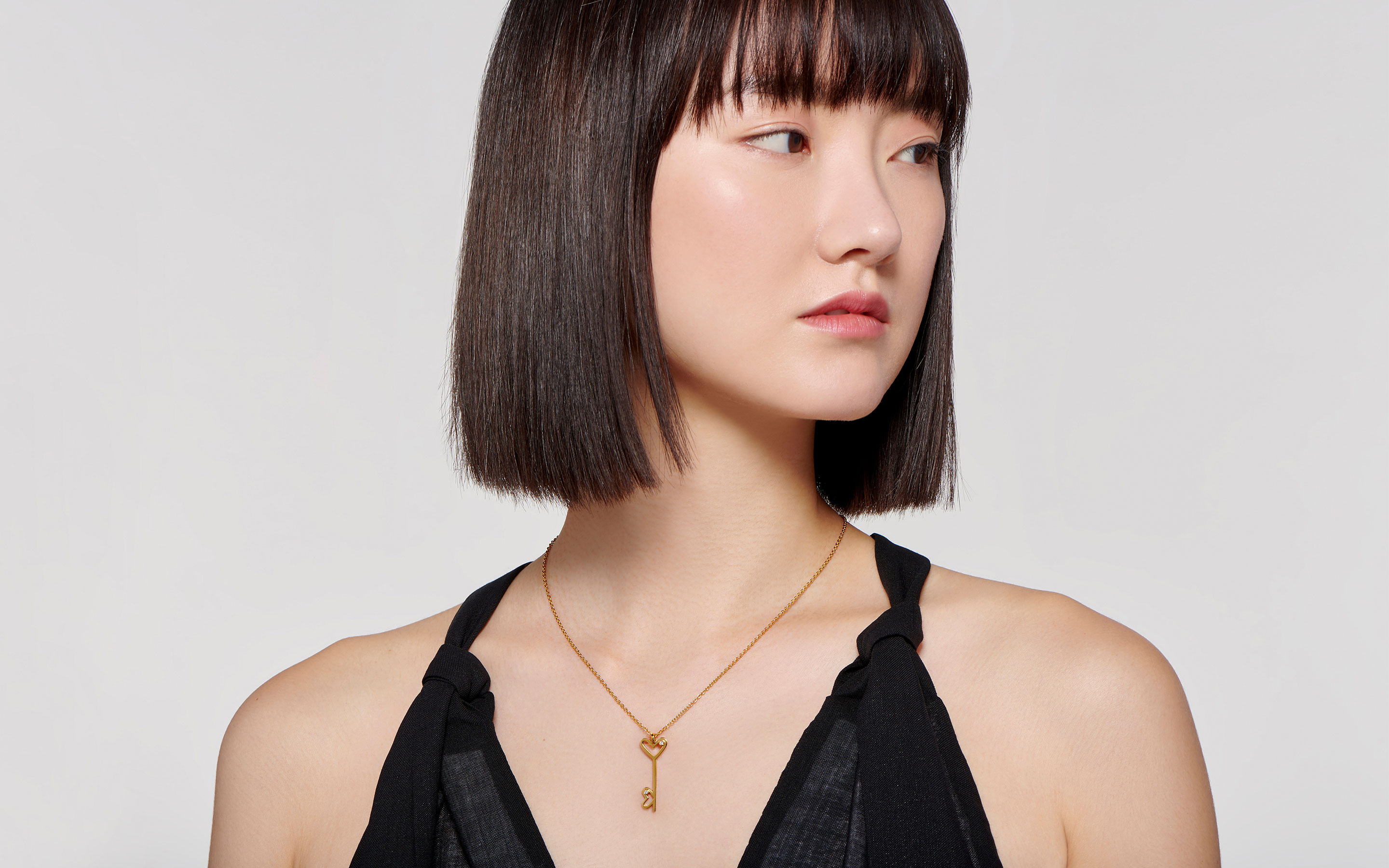 graceful East Asian woman modeling 22 karat gold necklace with double heart key pendant