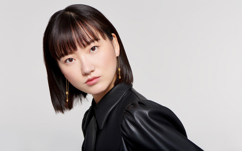 elegant East Asian female model with trendy arrow-shaped threader earrings in 22 karat gold