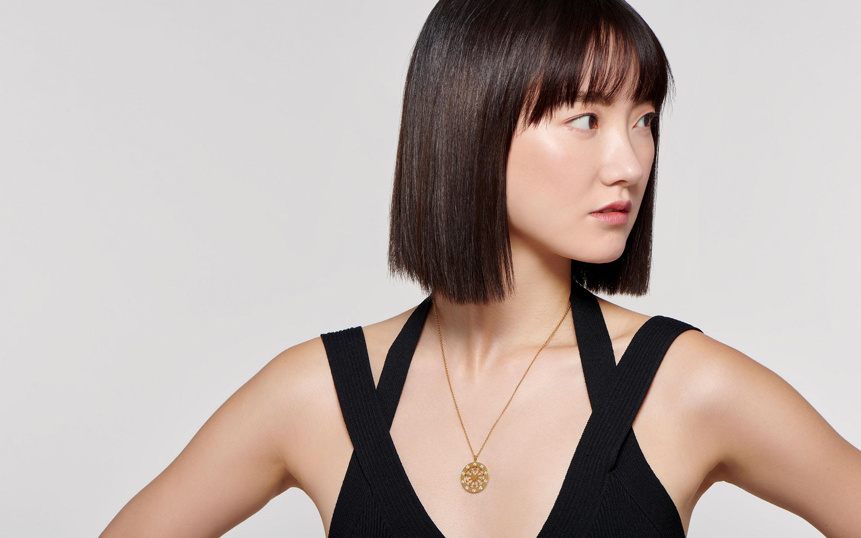 elegant East Asian female model wearing sleek pendant medallion neck chain fashioned of 22 karat polished gold with diamonds