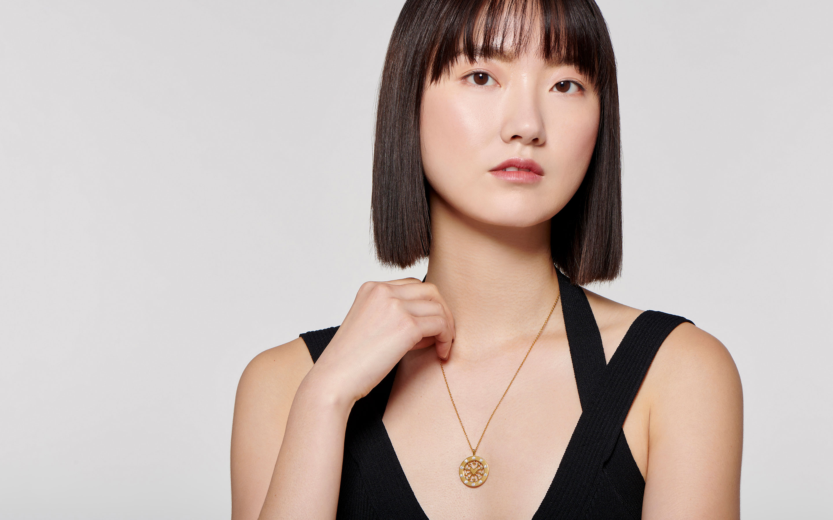 sultry East Asian woman showcasing stylish medallion necklace made of 22 karat polished gold with diamond accents