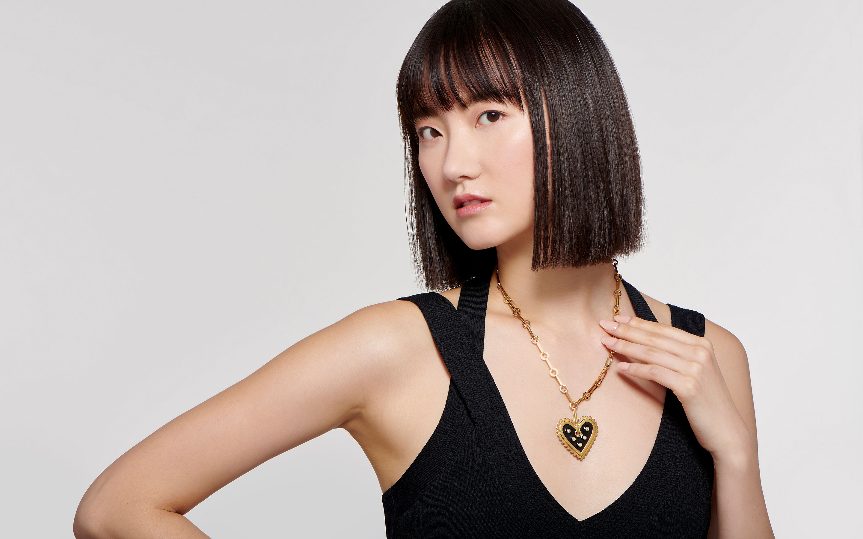 stylish East Asian woman showcasing 22 karat gold necklace with heart medallion and diamonds