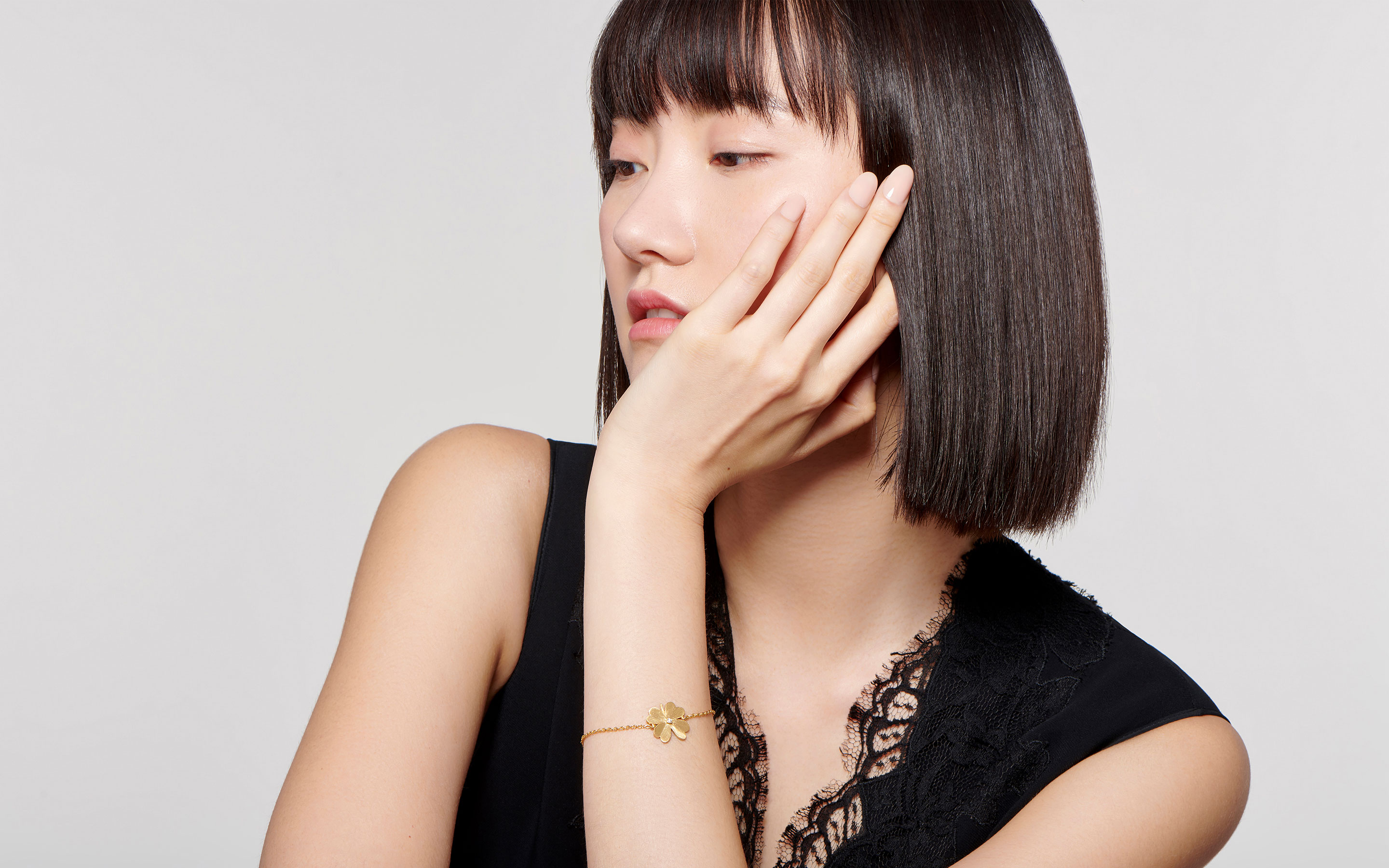 charming Asian model  sporting a pretty central cut round diamond on a satin finished 22 karat gold bracelet shaped in a four-leaf clover design