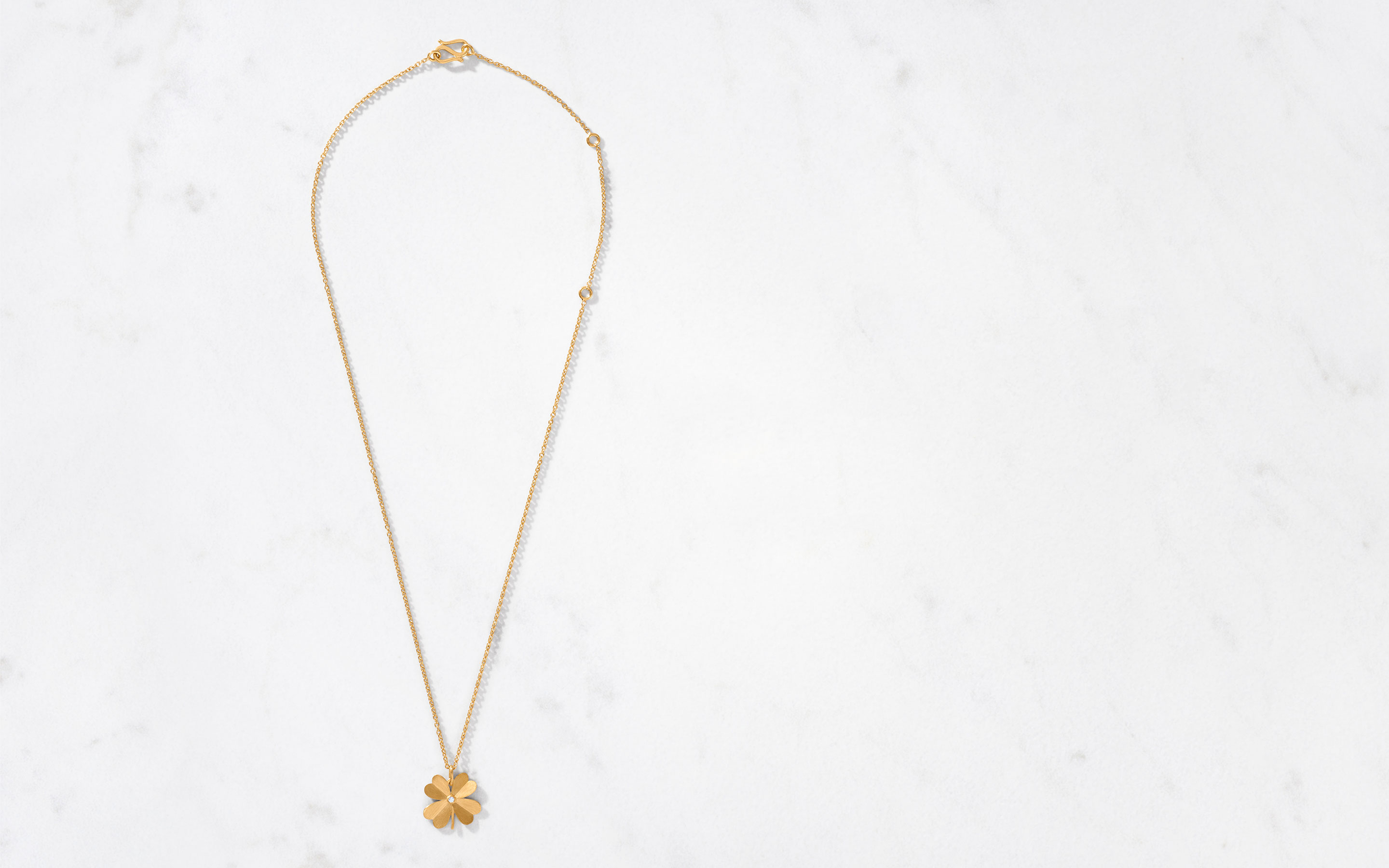 sophisticated 22 karat gold clover necklace satin finish with a center cut round diamond