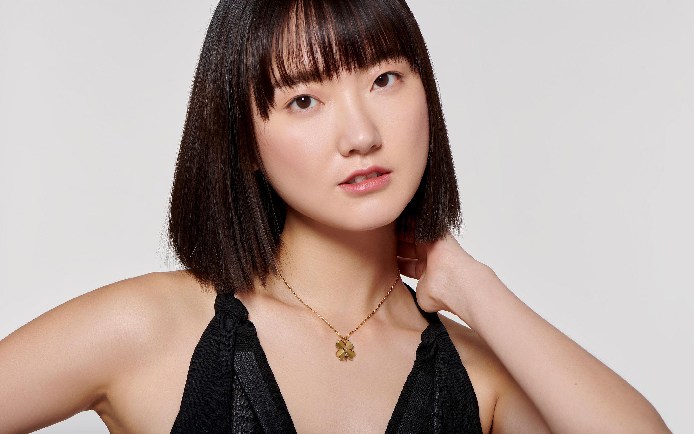 Asian model displaying dainty polished 22 karat gold necklace