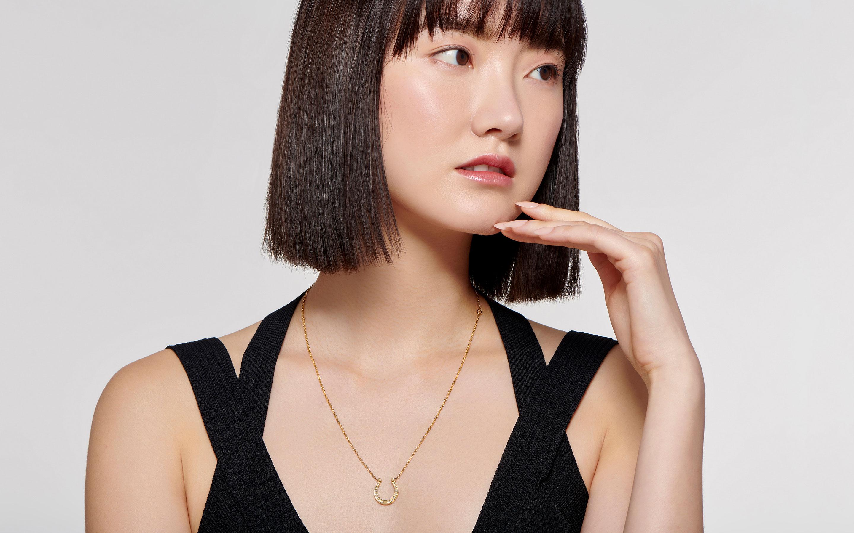 Elegant female model exhibits an ornate 22 karat gold horseshoe necklace embedded with 14 diamonds